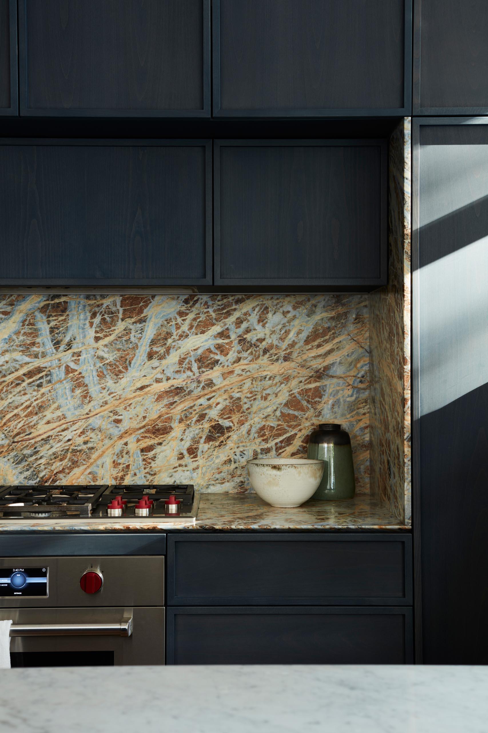 A modern kitchen with dark hardware free cabinets.