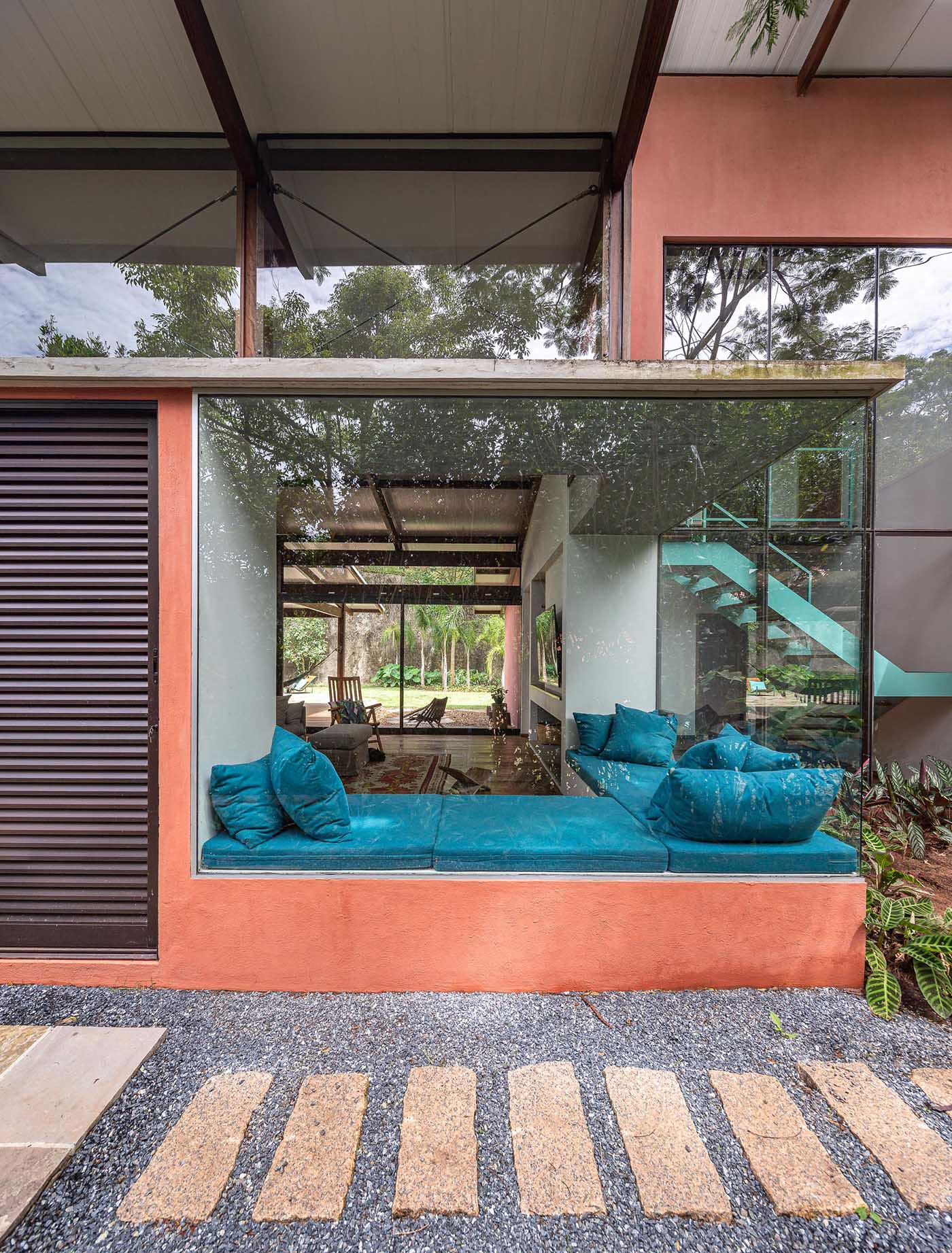 This modern window bench makes its home next to large windows and has has a height that matches the bottom of the glass, which can been seen from the exterior of the home.