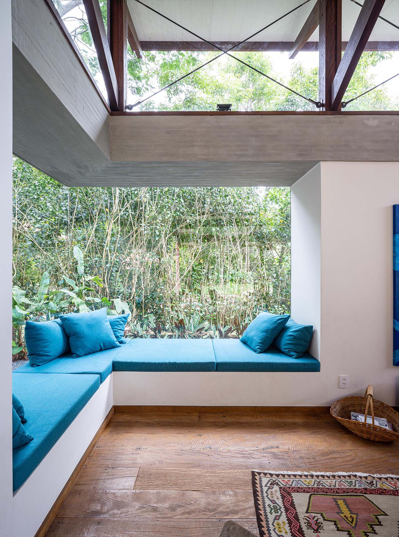 The bright blue upholstered cushions and pillows adds a bright and colorful accent to the room, while the window bench is long enough to accommodate multiple people.