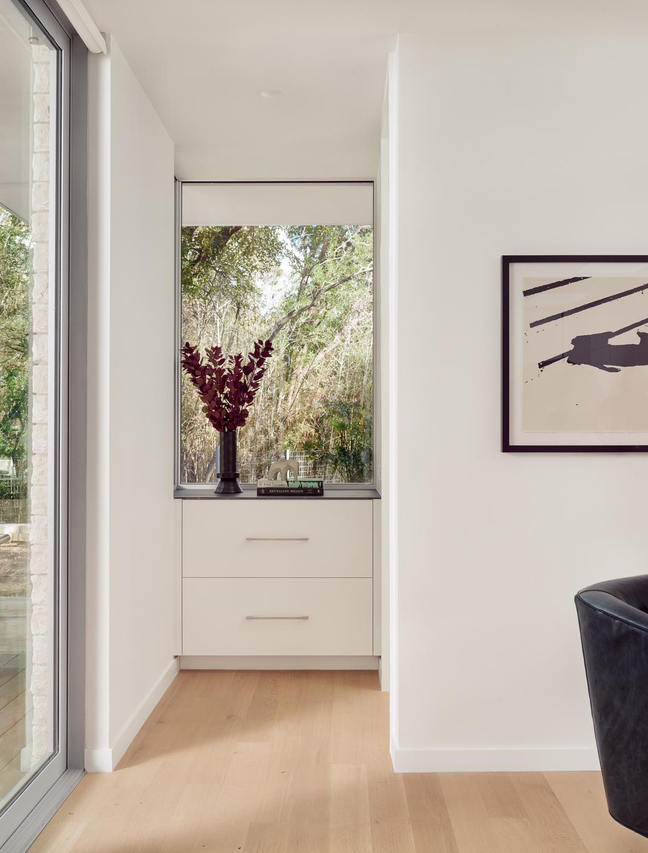 A modern white built-in dresser located beneath a window.