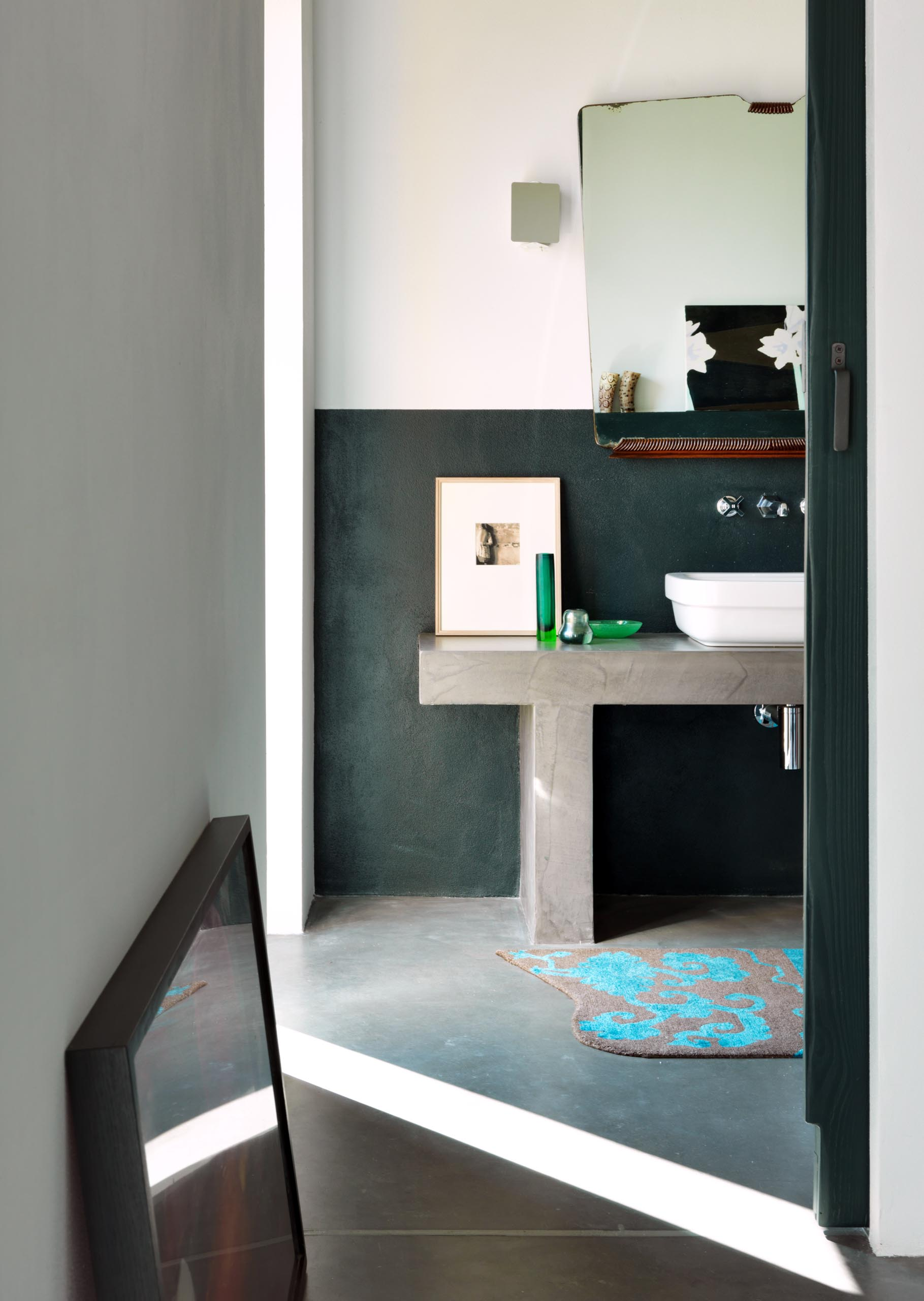 A contemporary bathroom with a partial black accent wall.