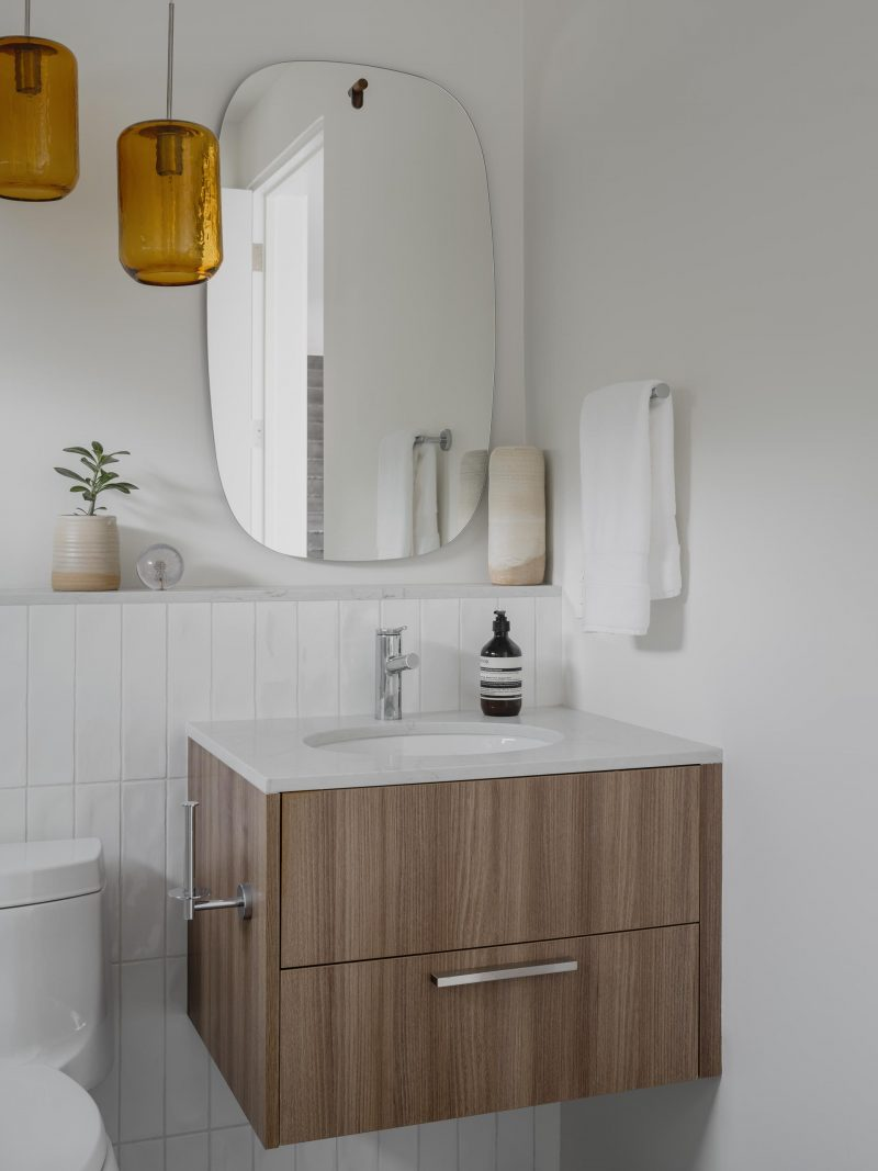 A modern bathroom with white walls and tiles, a floating wood vanity, and a rounded mirror.