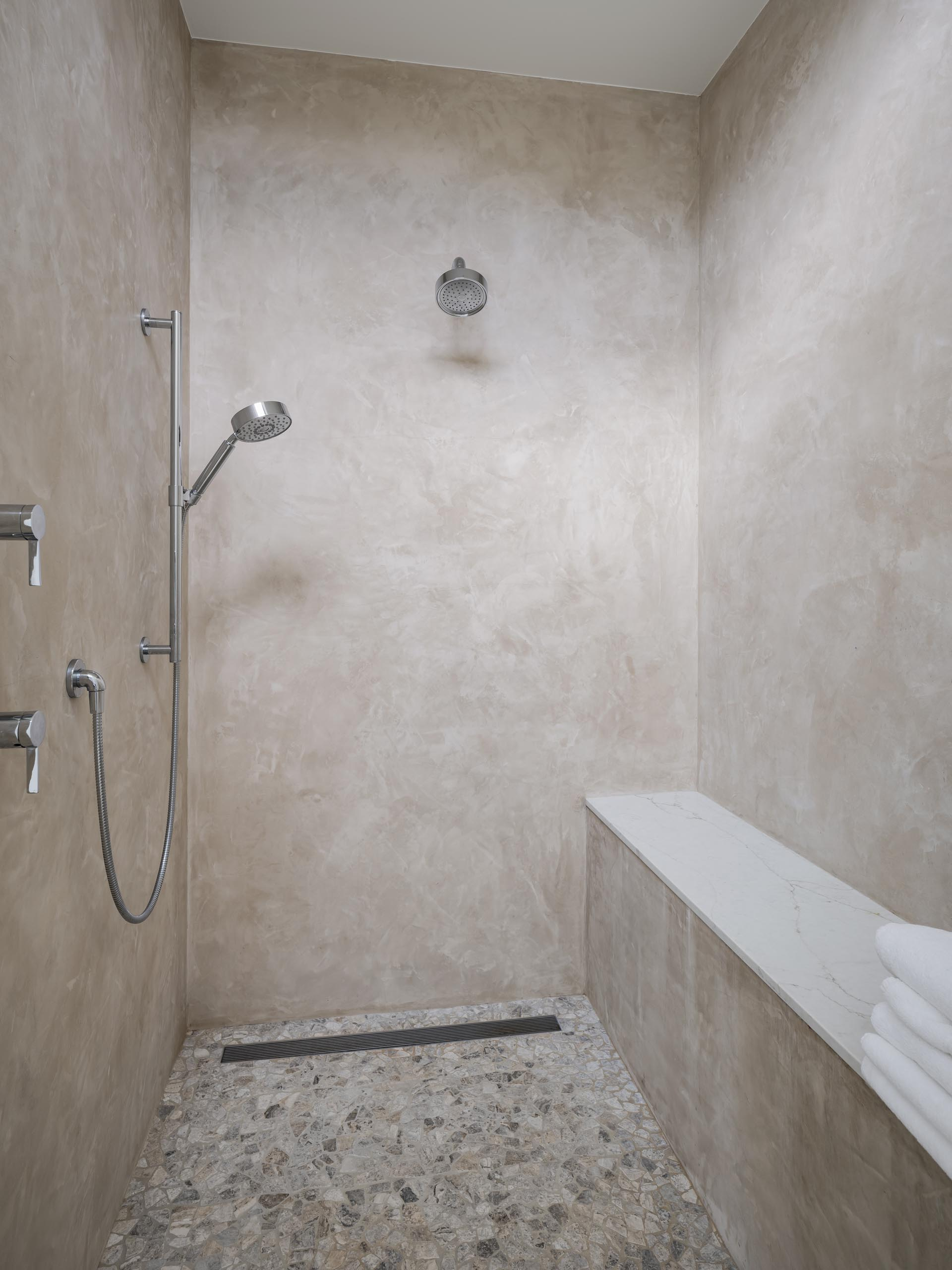 A contemporary shower with a built-in bench.