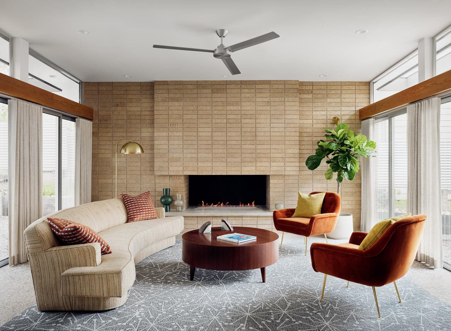 In this mid-century modern inspired living room, there's high ceilings and floor-to-ceiling windows that line the walls, while a brown brick fireplace is the focal point.