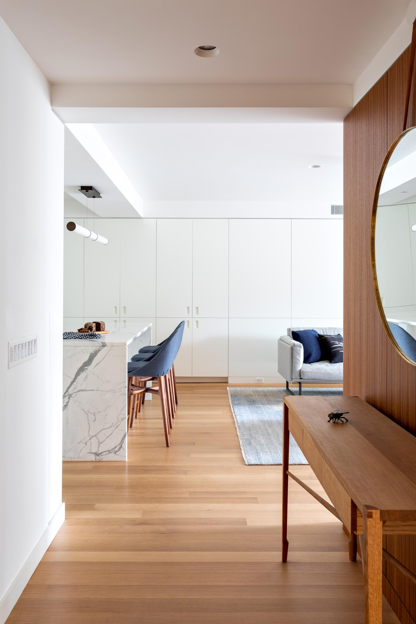 A modern apartment entryway with views of the white kitchen and gray furnished living room.