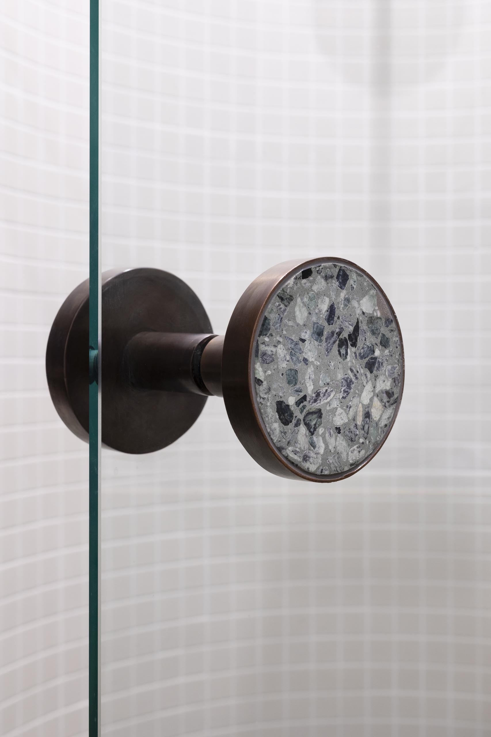 A glass shower screen with bronze hardware.