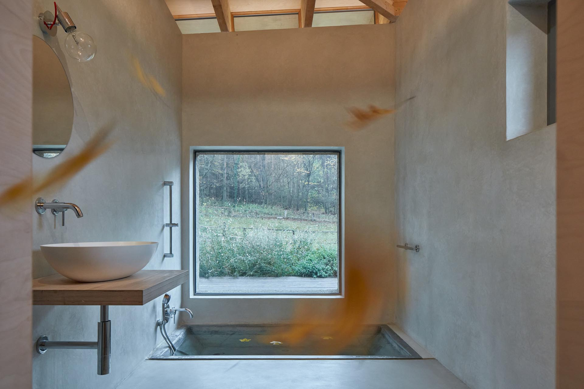 This modern cabin bathroom has been designed with a built-in sunken bathtub, a minimal wood vanity, and a large picture window.