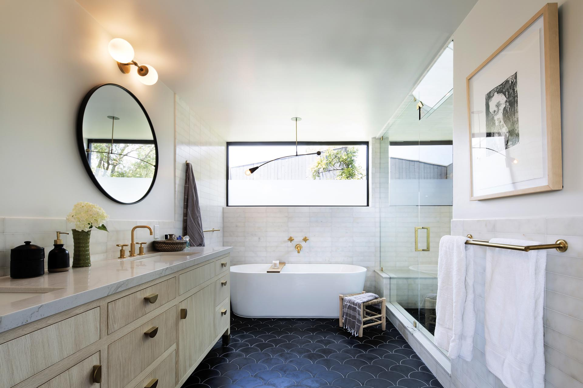 In this modern bathroom there's a double sink vanity with round mirrors, a freestanding bathtub, and a glass enclosed shower.