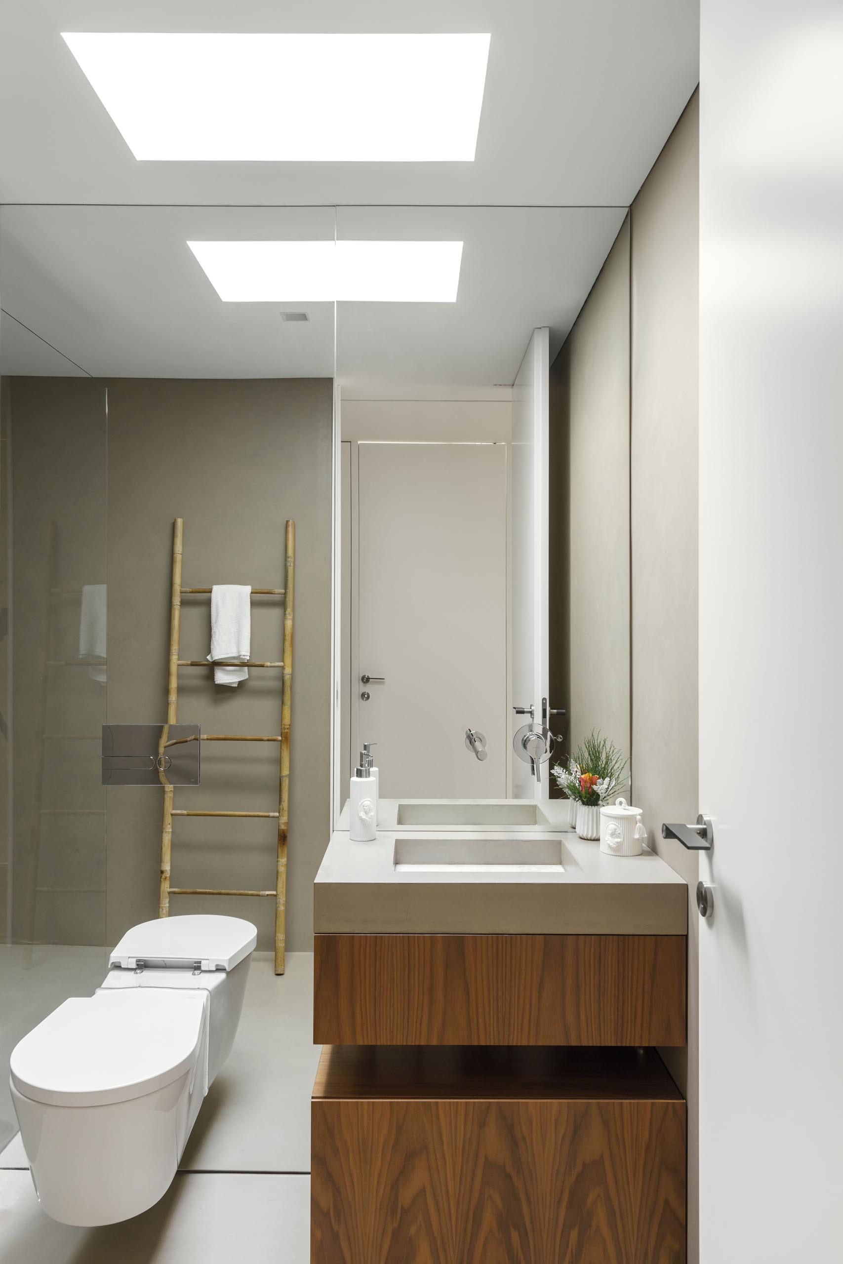 A modern bathroom with a built-in vanity sink and a floor-to-ceiling mirror.