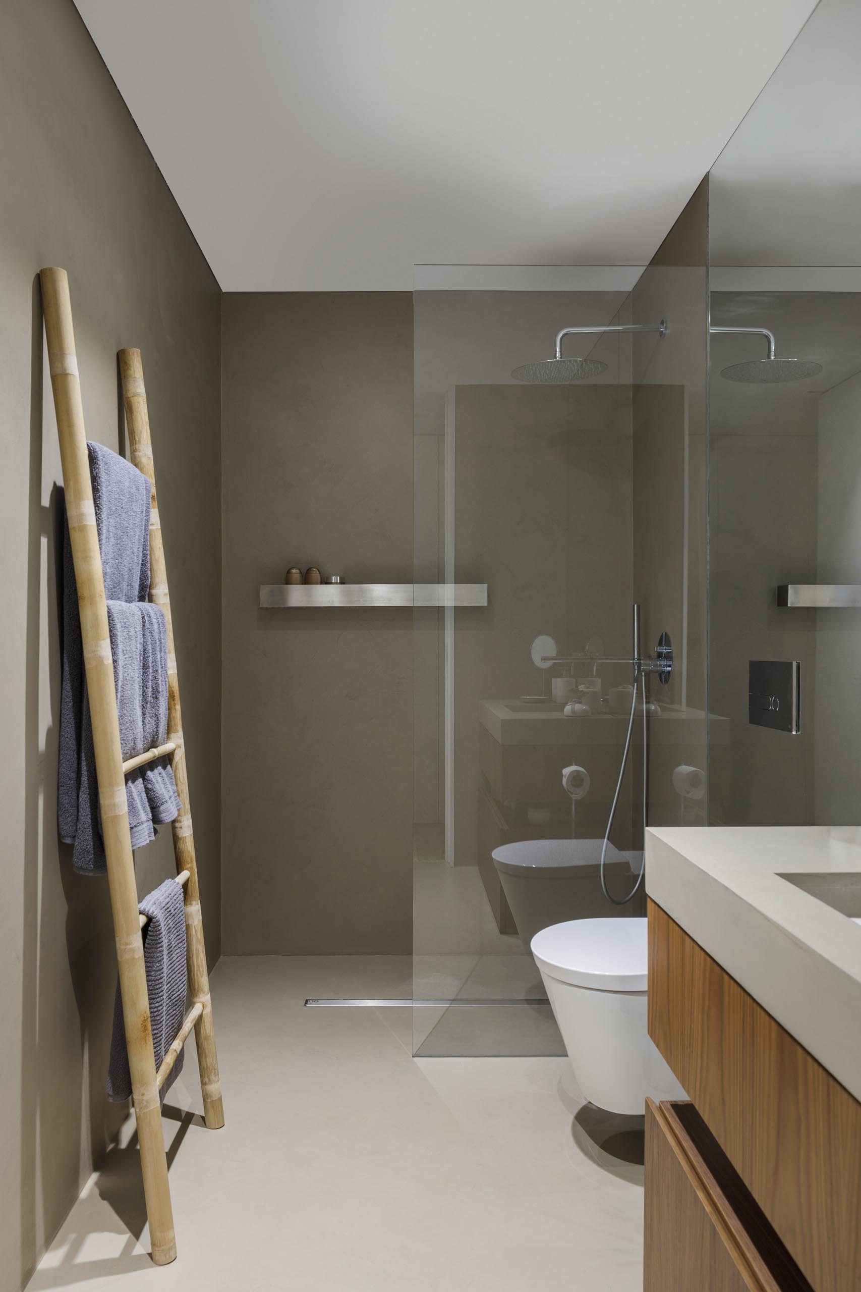 A modern bathroom with a floating shelf in the shower.