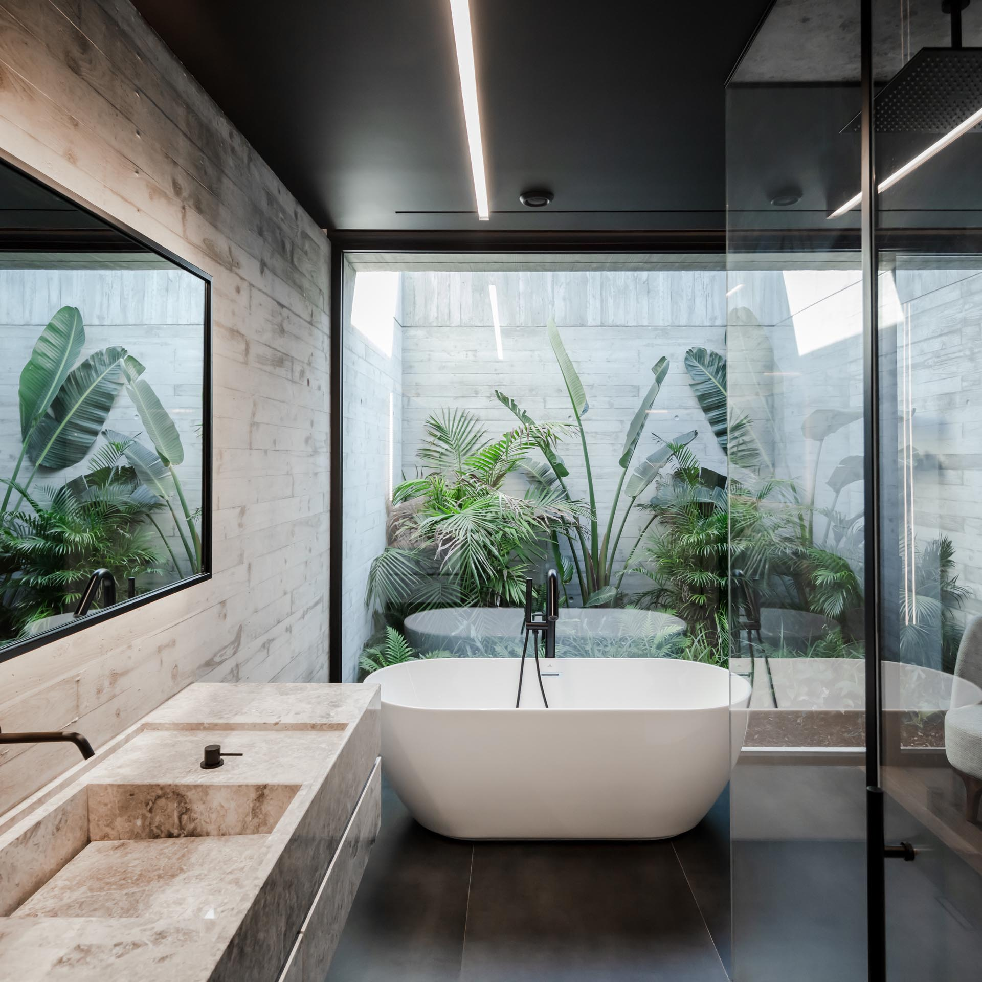 In this modern bathroom, there's a glass wall behind the freestanding bathtub that provides views of a tropical garden.