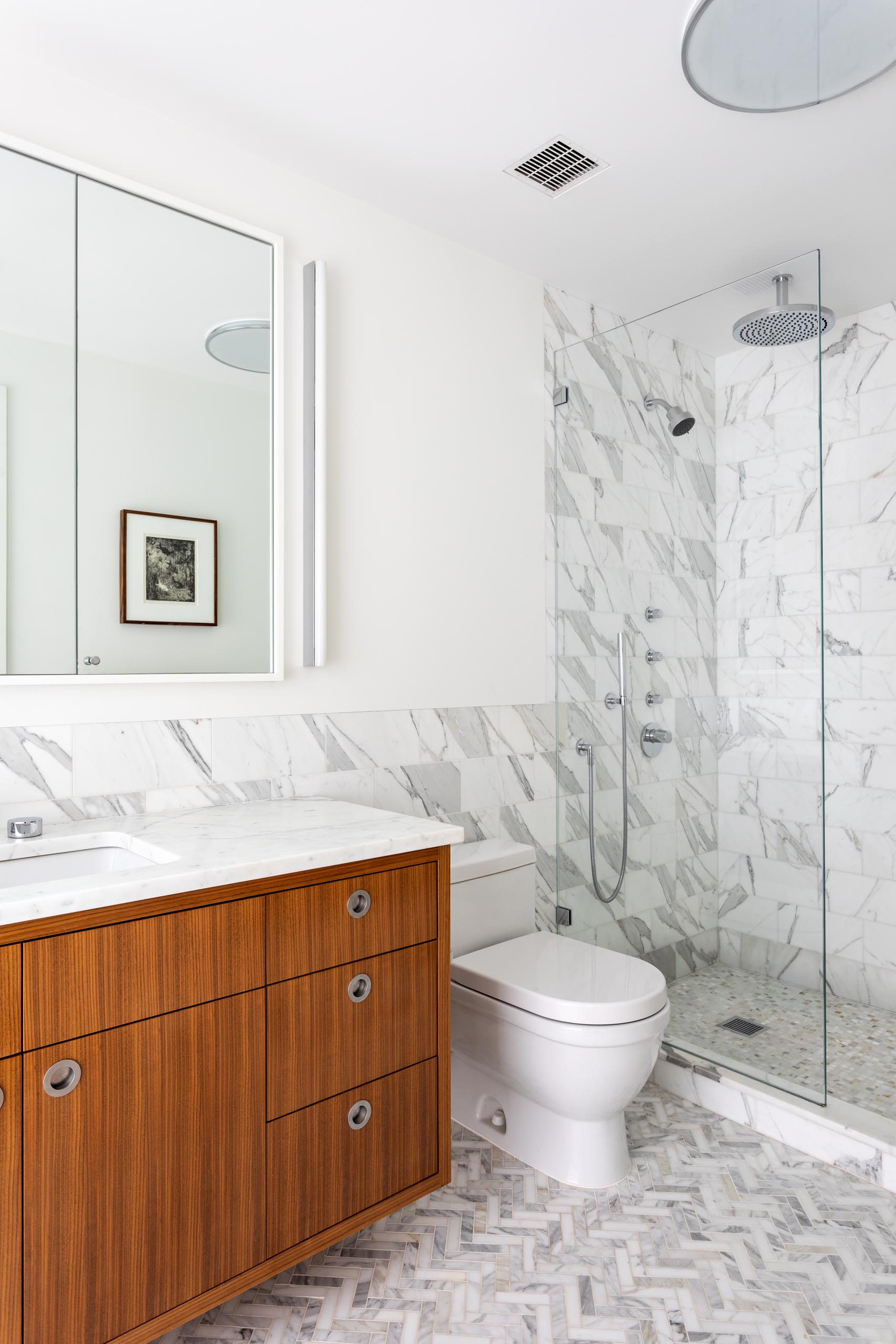 In this mdoern bathroom, there's a floating wood vanity with a tri-panel mirror mounted to the wall, and a marble backsplash that continues through to the shower.