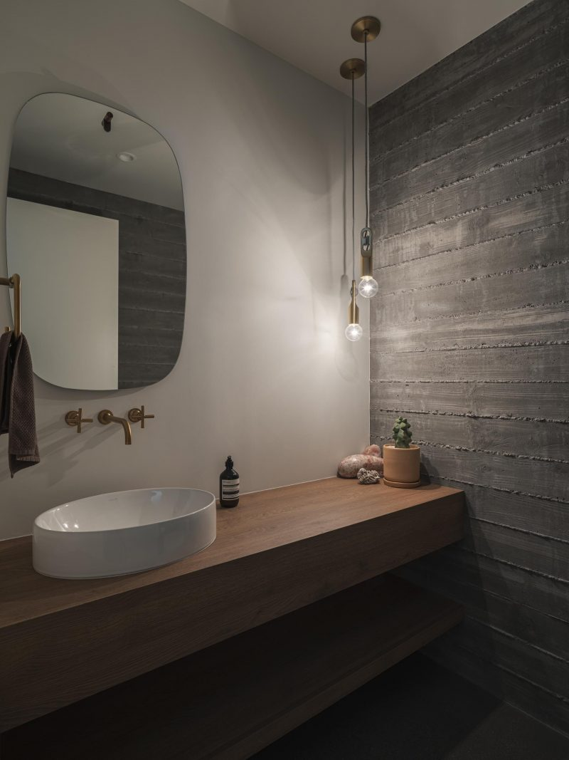 A modern bathroom with board formed concrete wall, a wood vanity, and a rounded mirror.
