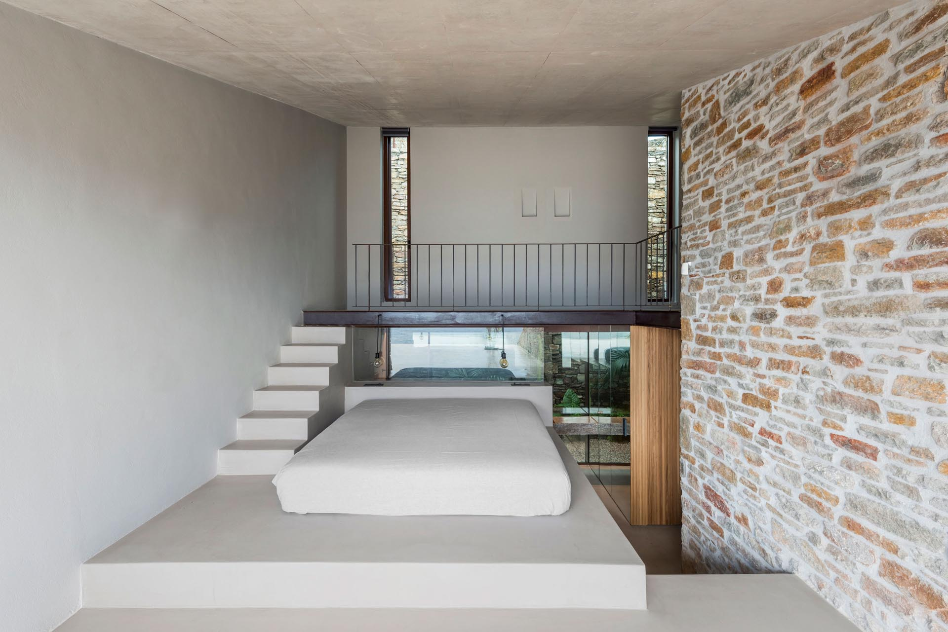 A minimalist bedroom with a bed raised on a platform to take advantage of water views.