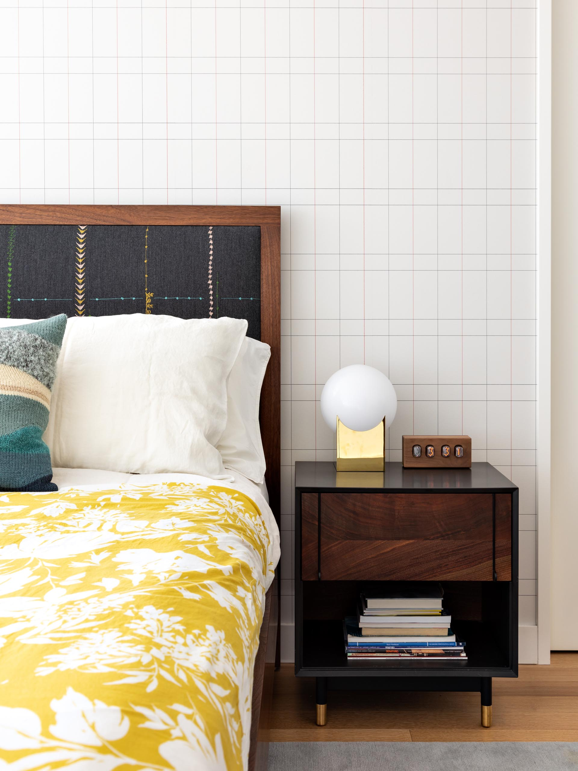 A modern master bedroom that includes wood furniture, pops of color, and a graphic accent wall.