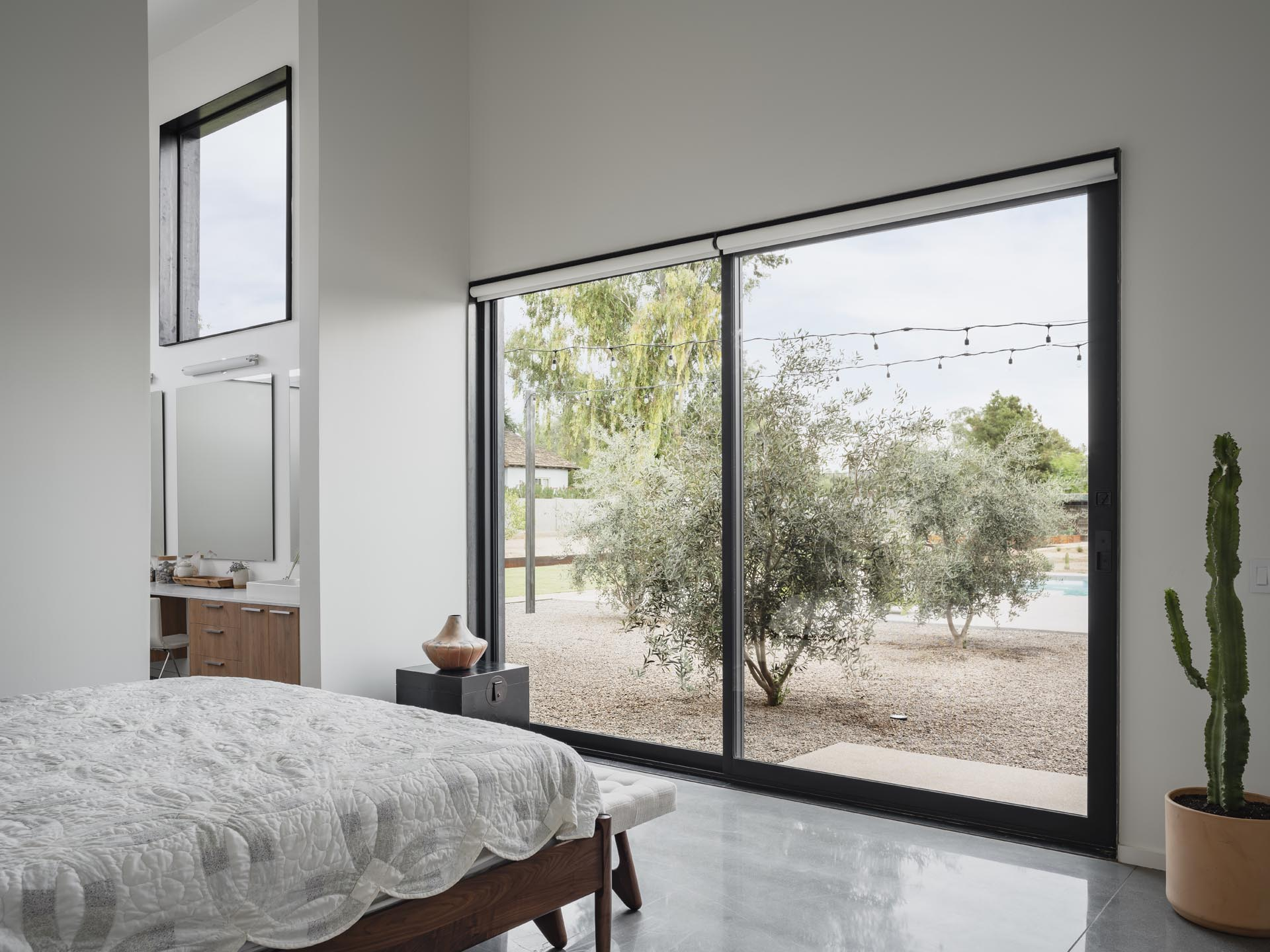 In this modern master bedroom, high ceilings create a lofty and open room, while a sliding door connects to the outdoors.