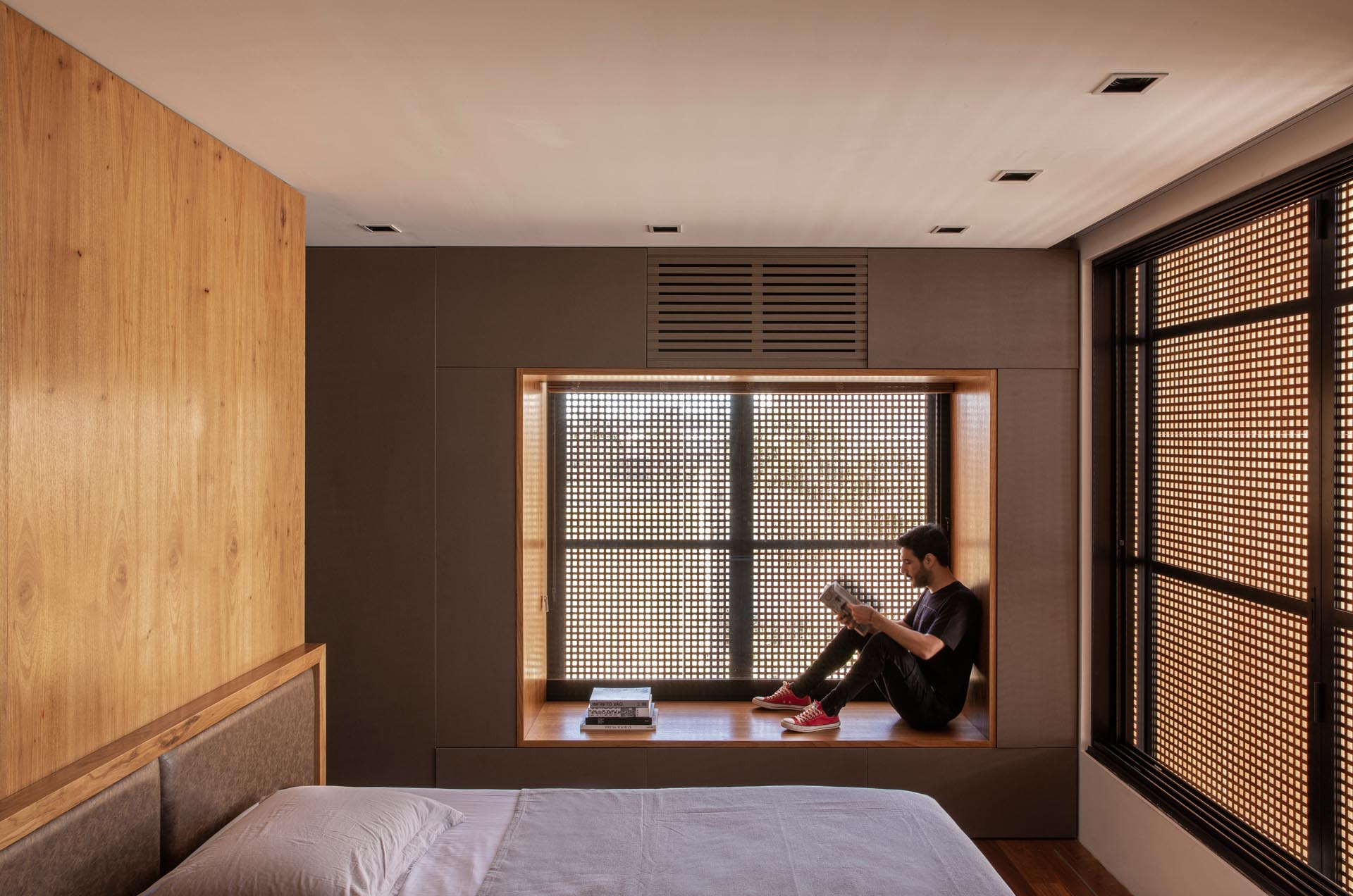 In this modern bedroom, there's a wood lined window seat that acts as a small reading nook. The louvers on the exterior of the home provide shade and privacy without blocking the natural light.