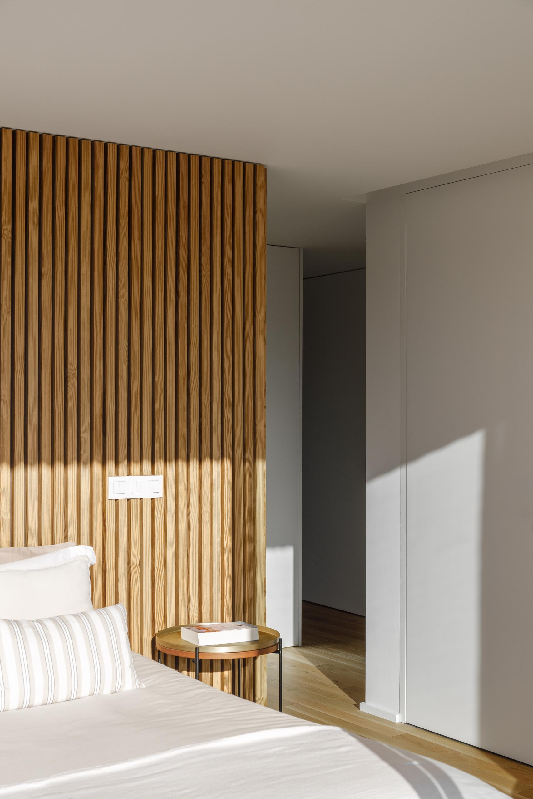 A modern bedroom with a wood slat accent wall.