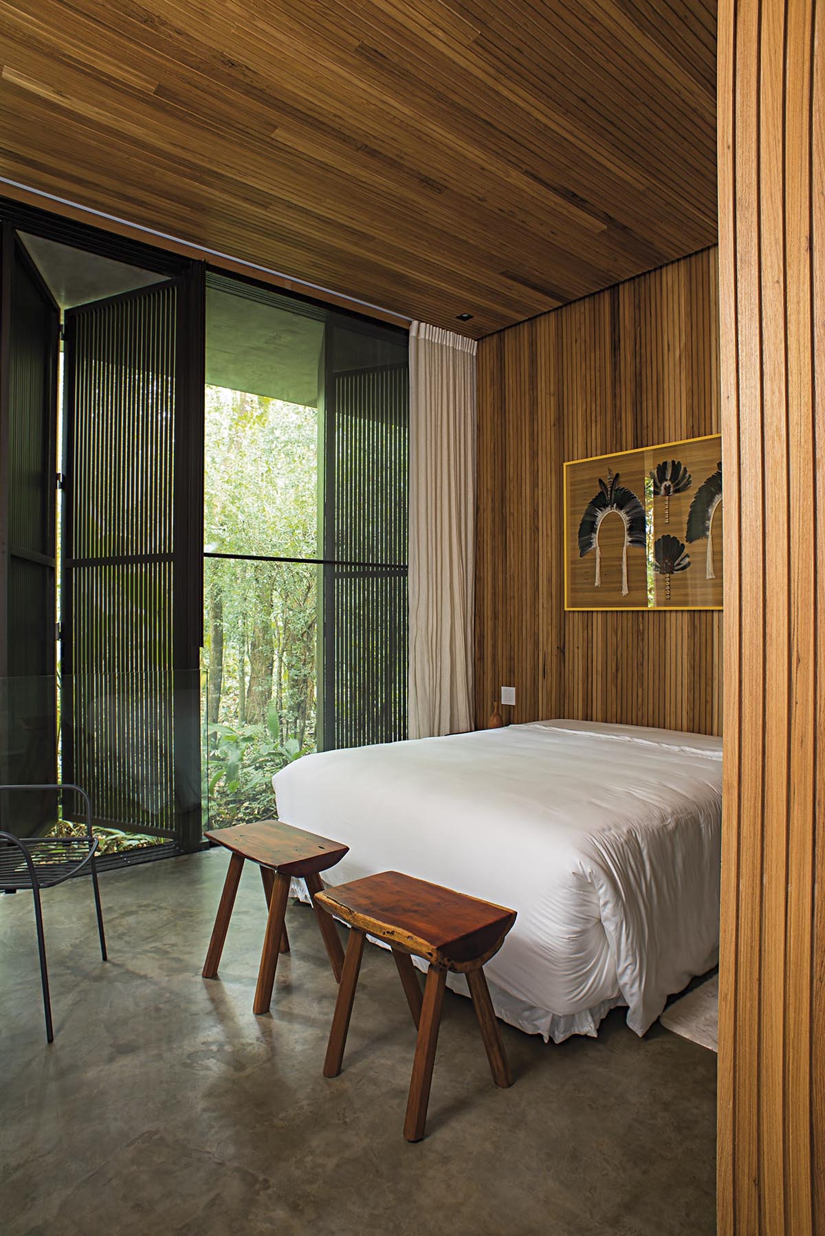 In this modern bedroom the wood ceiling carries on to the wall, creating a backdrop for the bed and artwork. Wood shutters create privacy, however when open, they allow the natural light to flood the room.