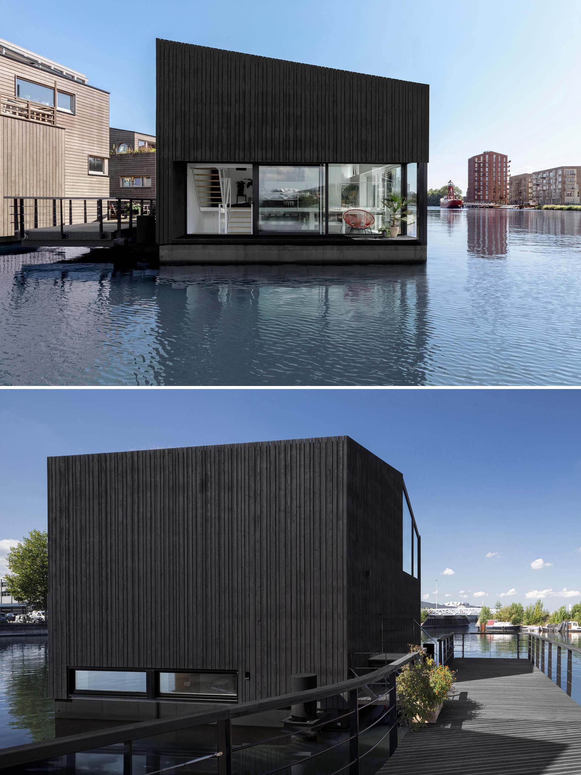 A modern float home with black wood siding and large windows.