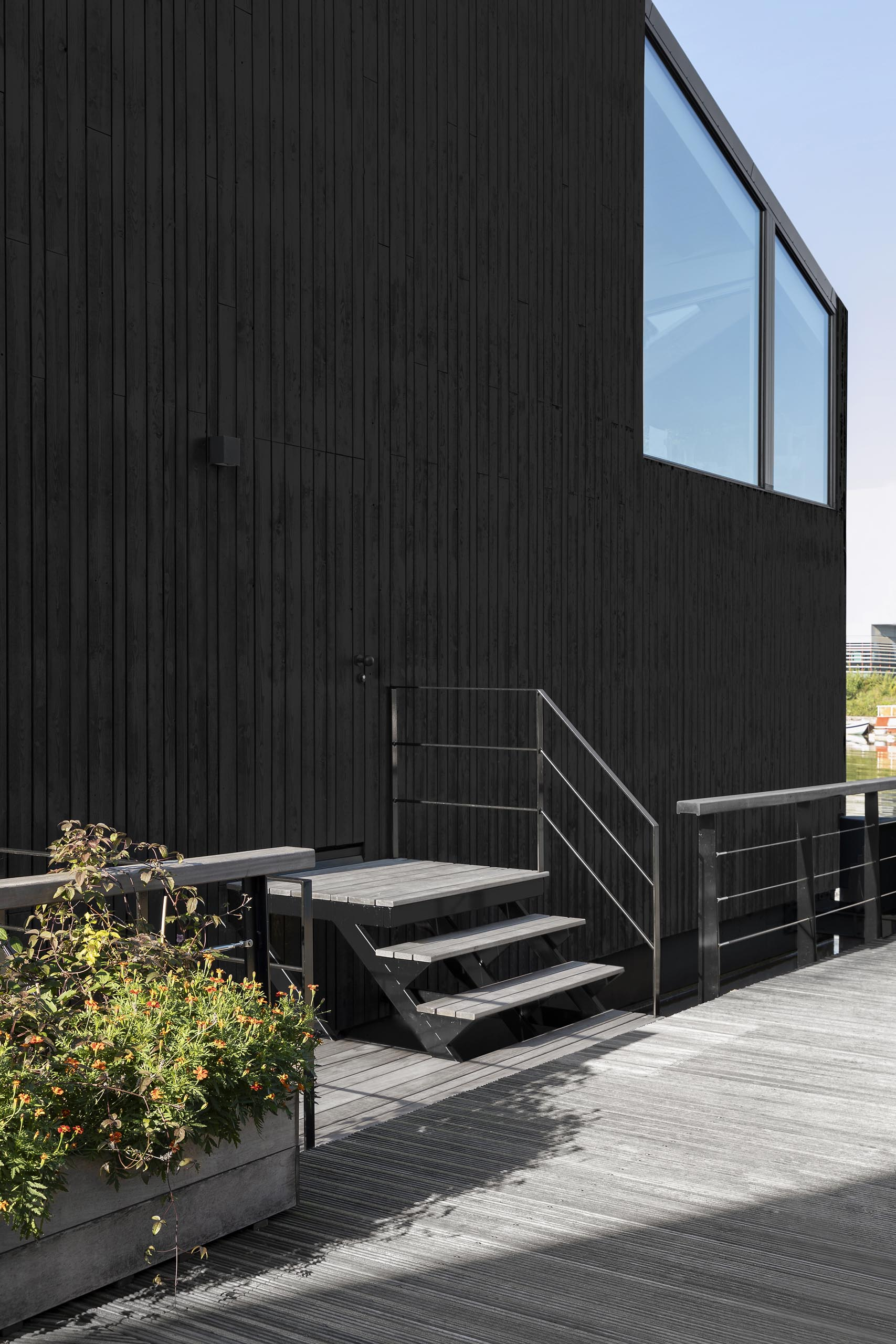 A modern float home with black wood siding.