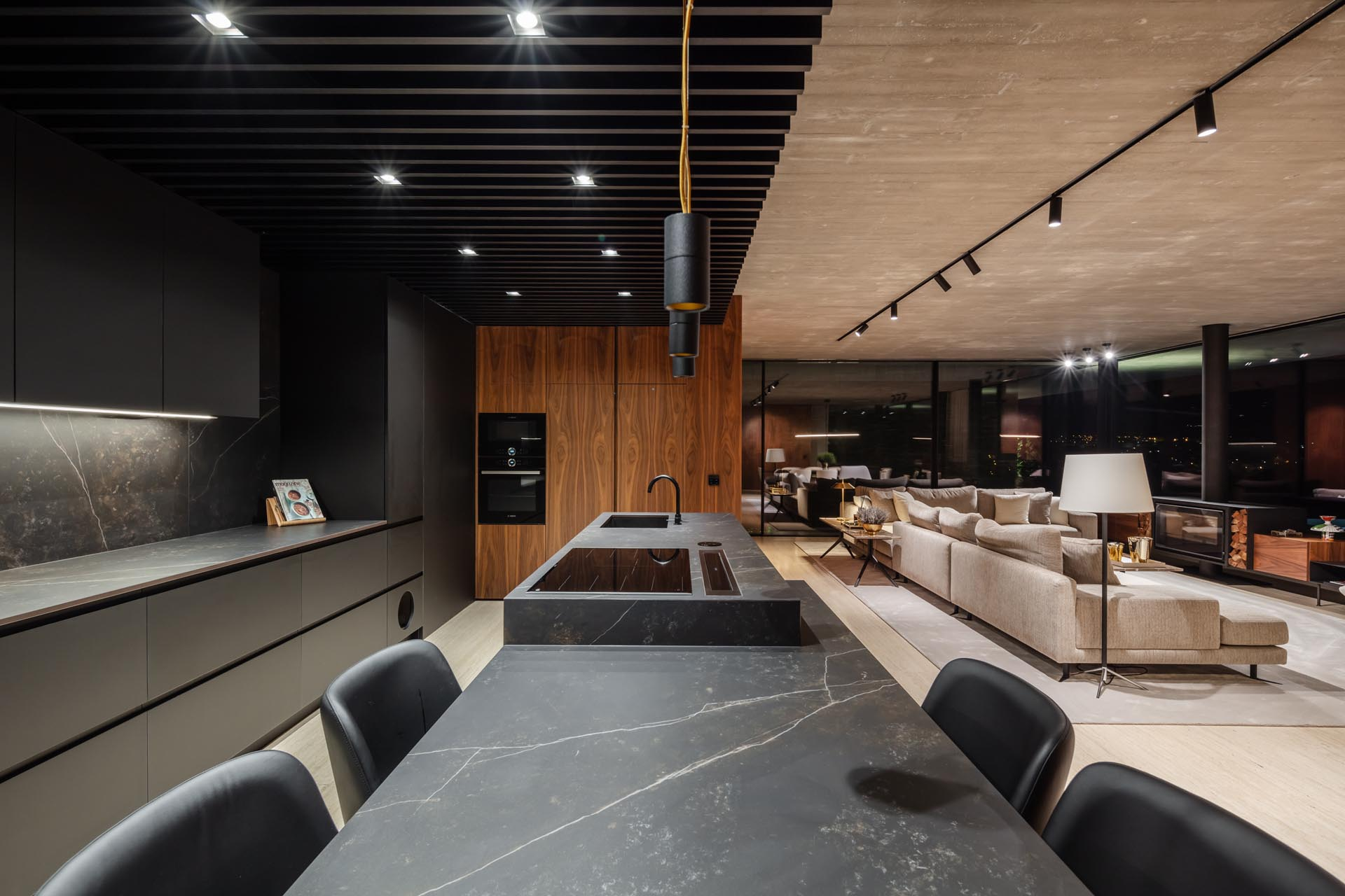 A modern black kitchen includes a large island with dark gray stone, seating for four people, a cooktop, and a undermount sink.