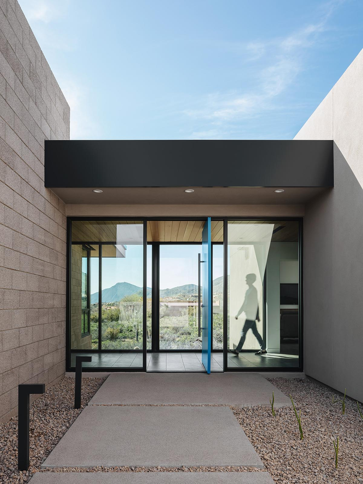 A modern desert home with bright blue pivoting front door.