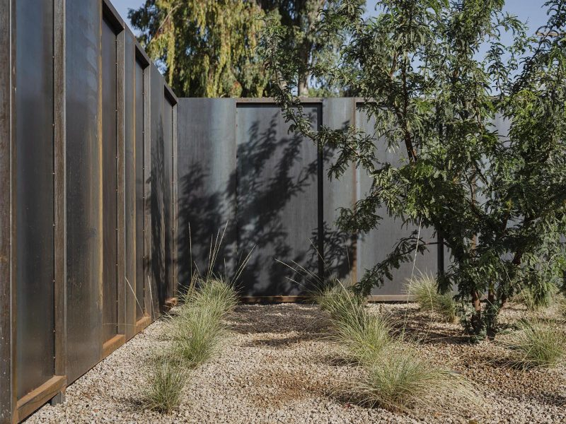 A modern steel fence with minimal landscaping.