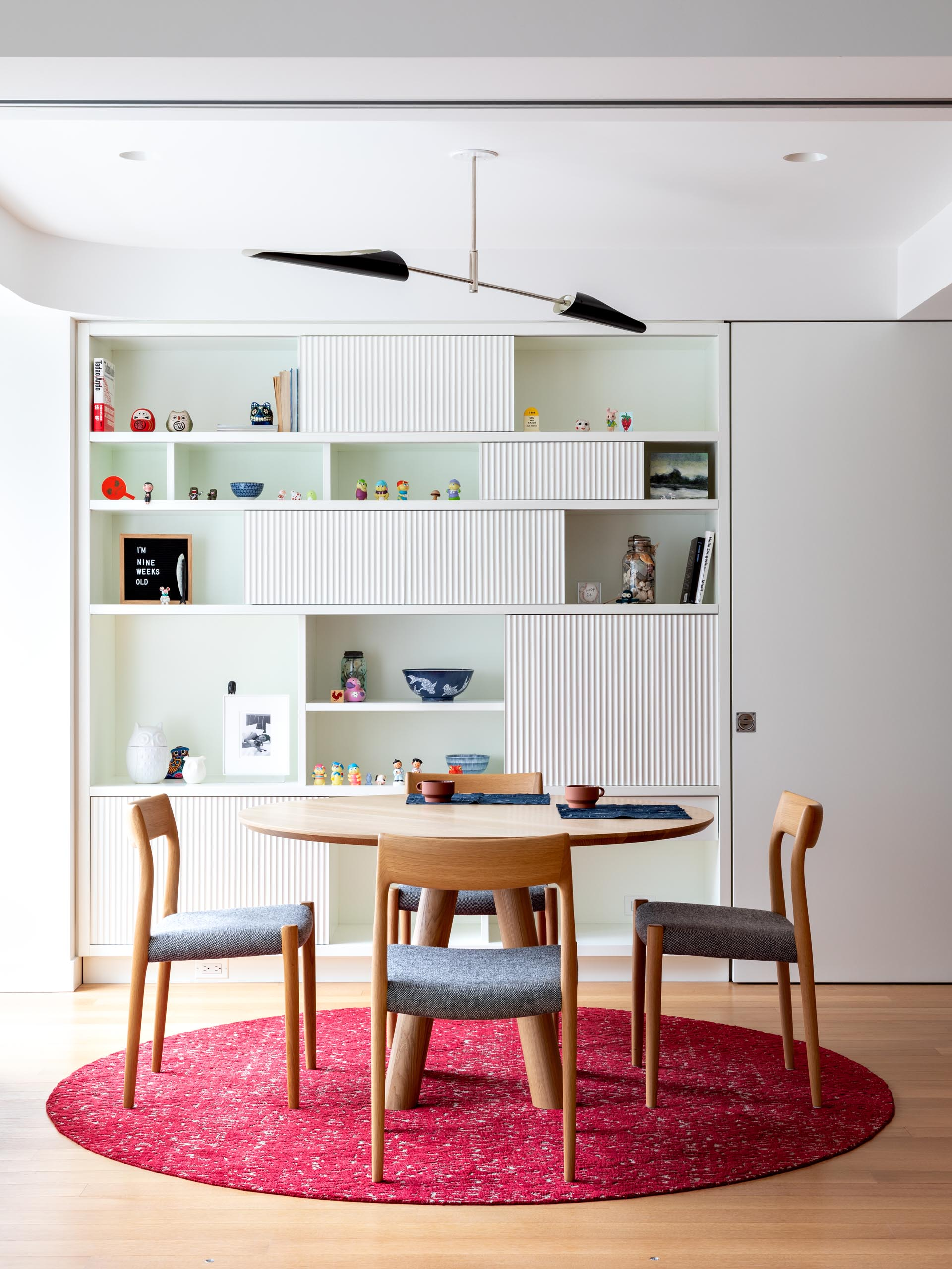 This modern dining room has a large bookshelf with textured panes that's used for displaying decorative items.