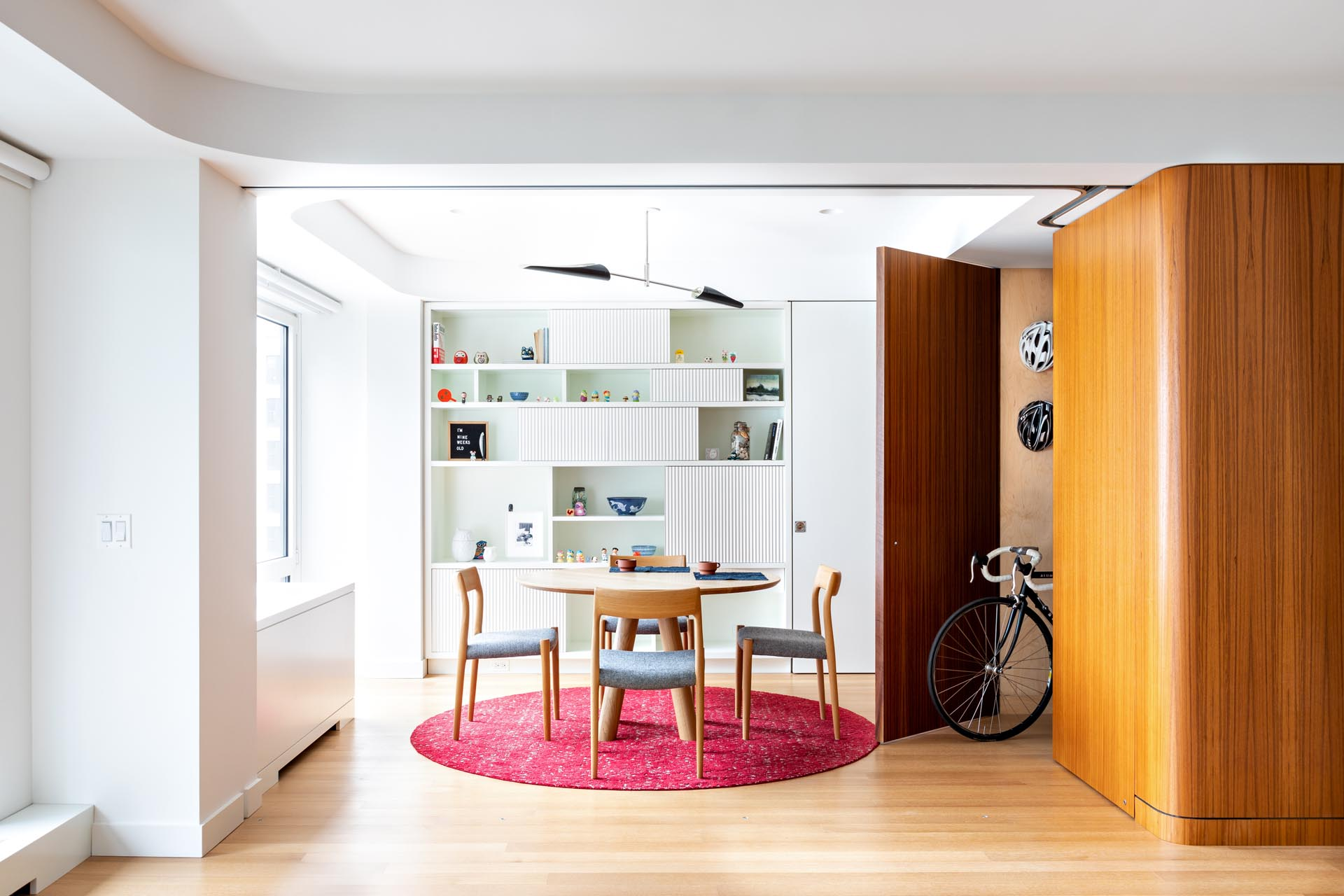This modern apartment has a teak cube that's been designed with a door that opens to a storage room.