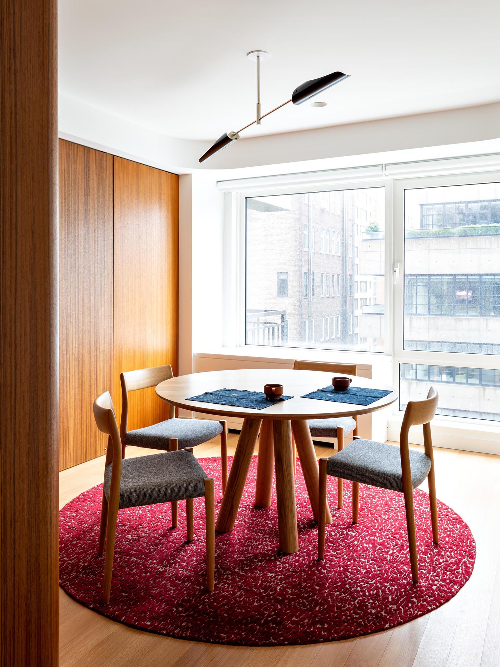 A modern dining room with a colorful burgundy/pink rug with wood furniture.