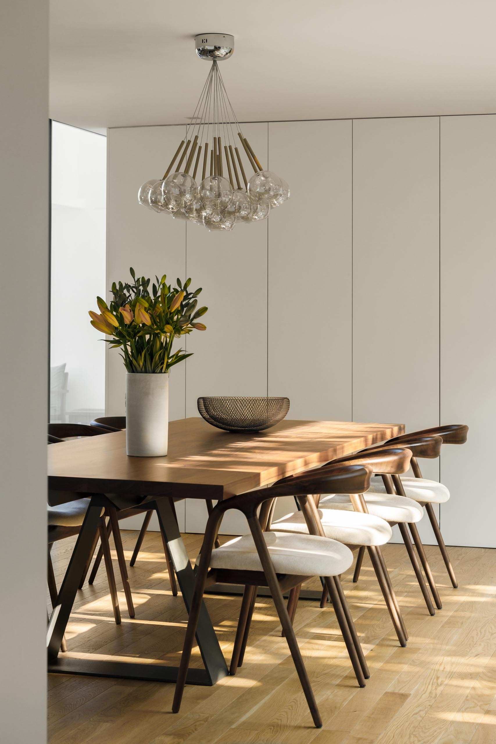 This modern open plan dining area has been furnished with a large wood table and chairs with upholstered seat cushions.