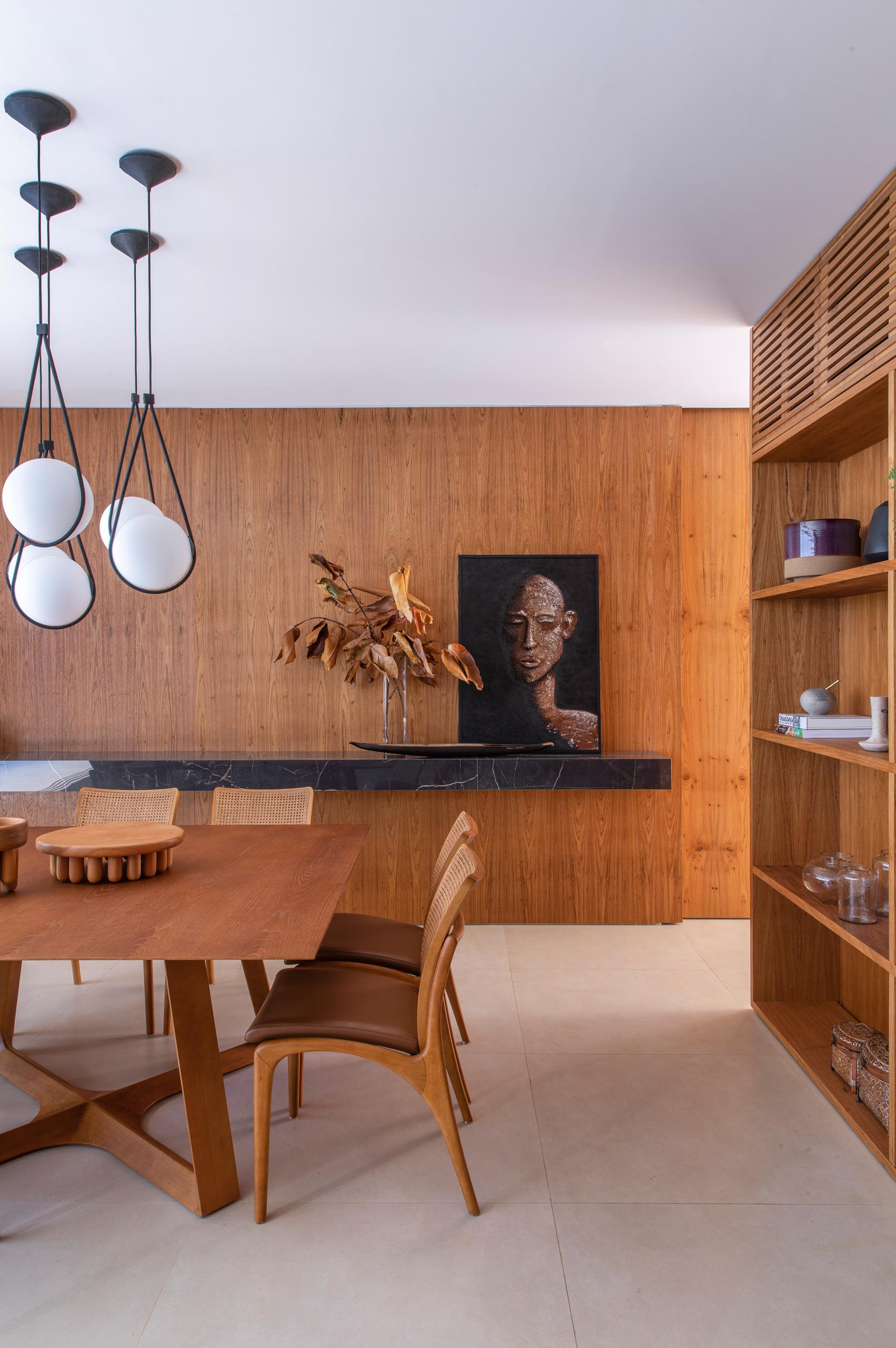 A modern dining room filled with wood and a floating black stone shelf.