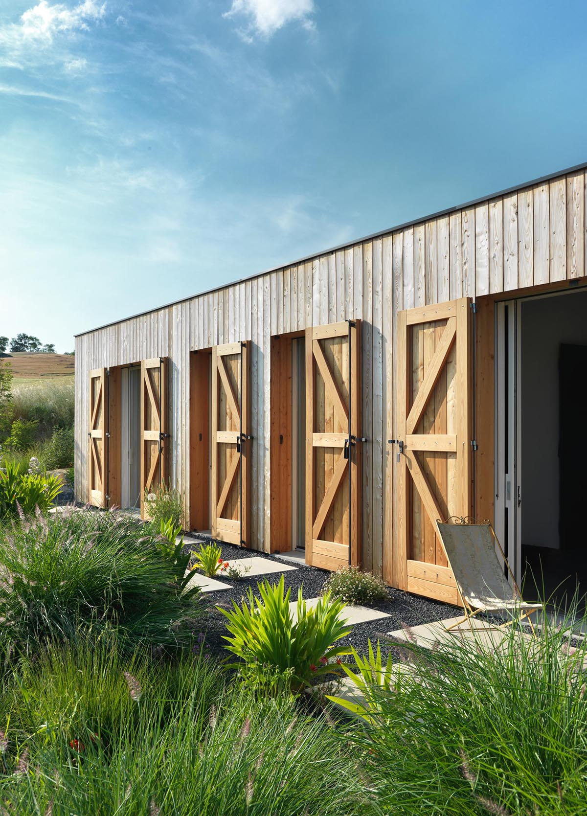 A modern farmhouse with wood shutters to protect the windows and doors.
