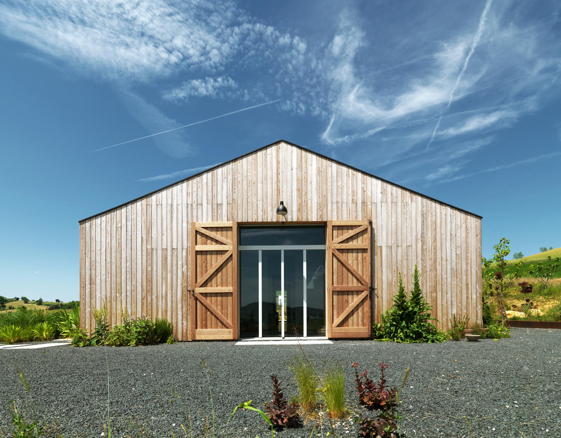The exterior of this modern farmhouse is clad with natural larch wood and shutters.