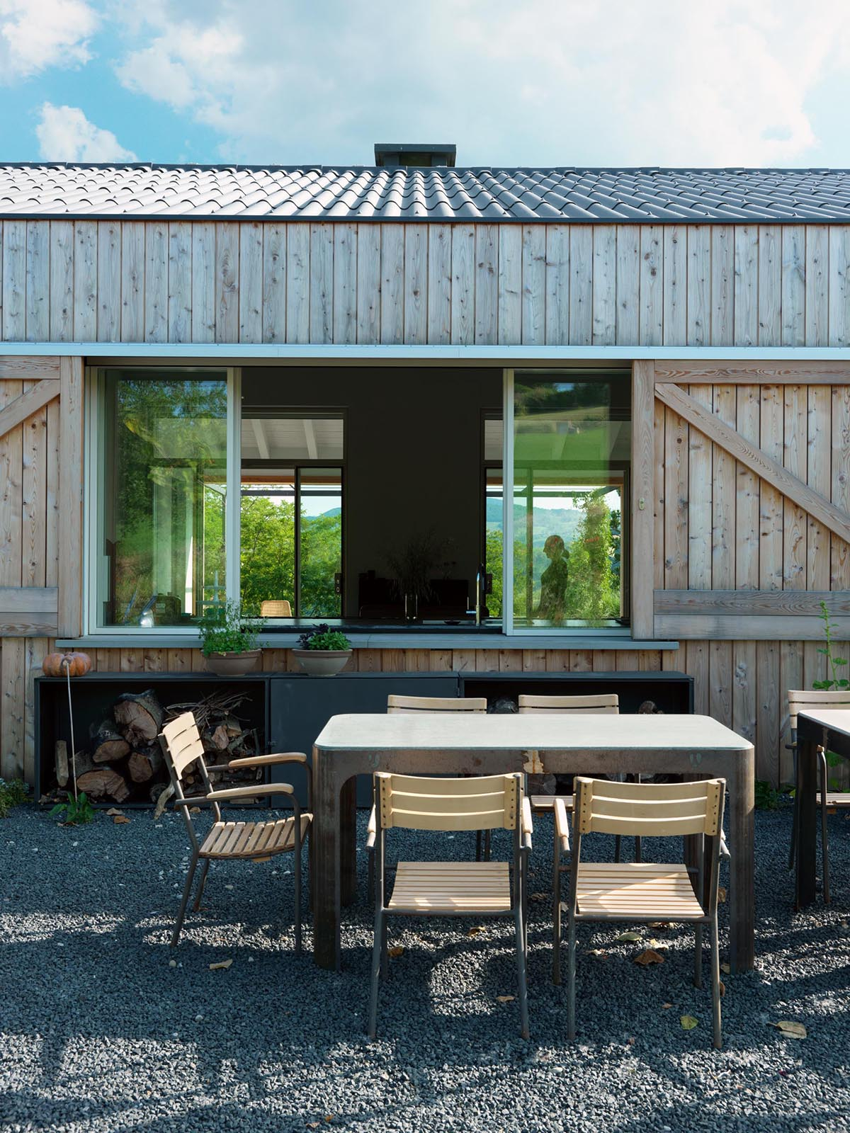 A modern country house with outdoor dining and sliding windows that act as a pass-through to the kitchen.