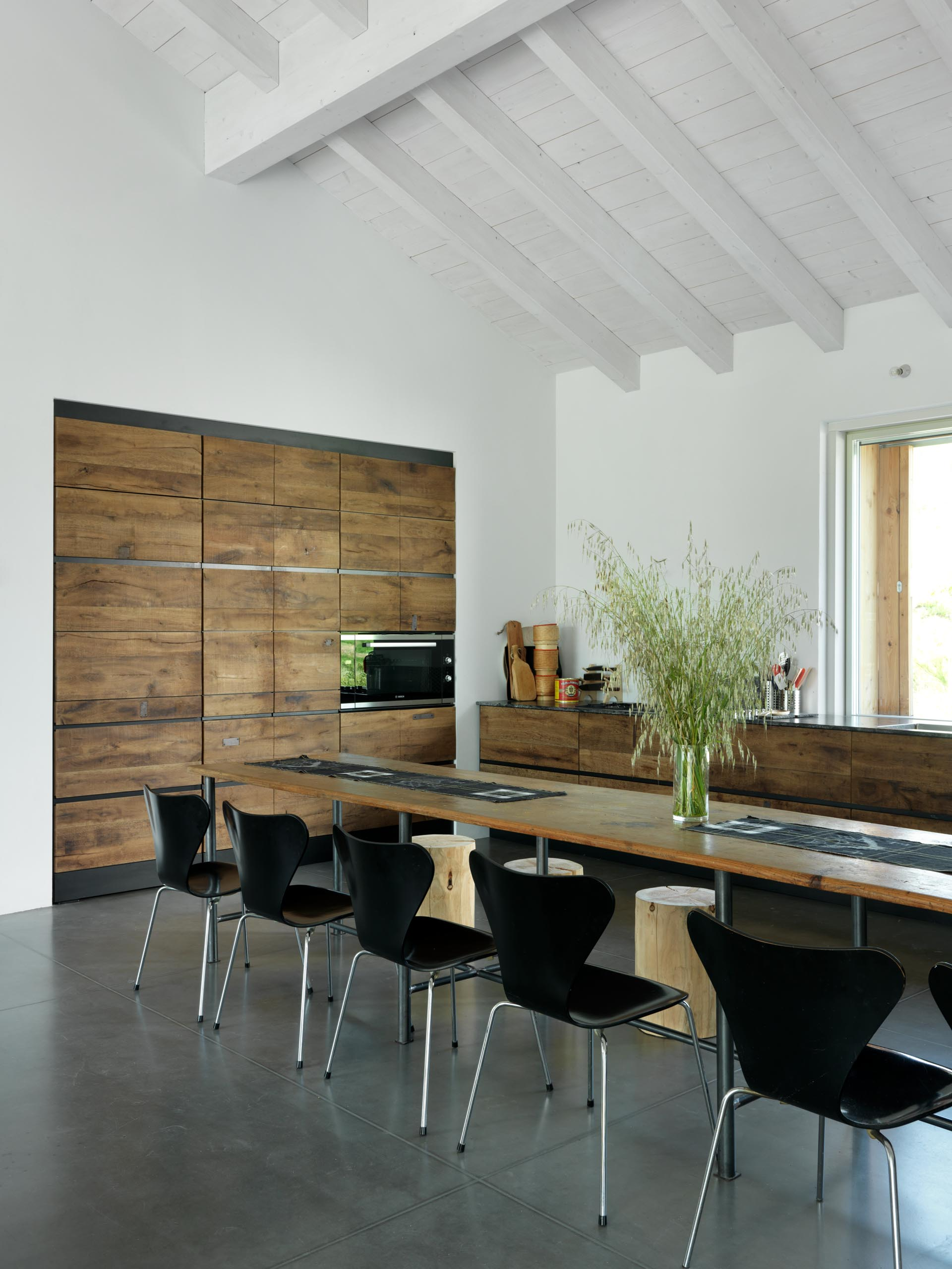 The custom made kitchen in this modern home has been achieved by using reclaimed wood, adding to the farmhouse aesthetic.