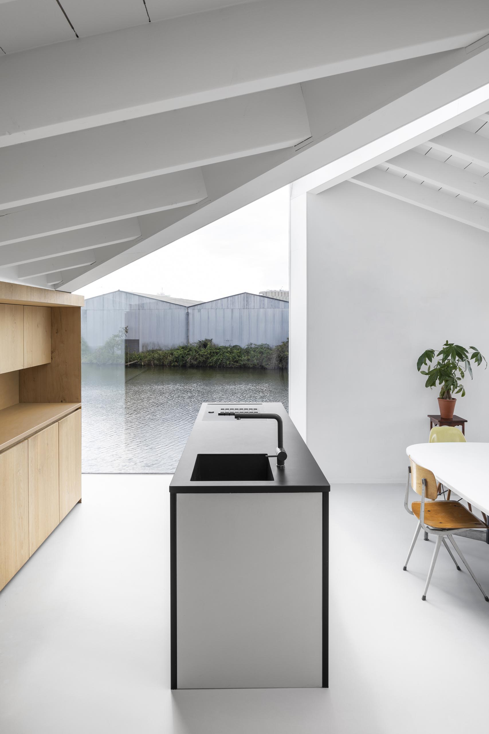 In the kitchen of a modern float home, a wall of wood cabinets is complemented by an island with a black countertop. An abundance of windows helps to keep the interior bright and open.