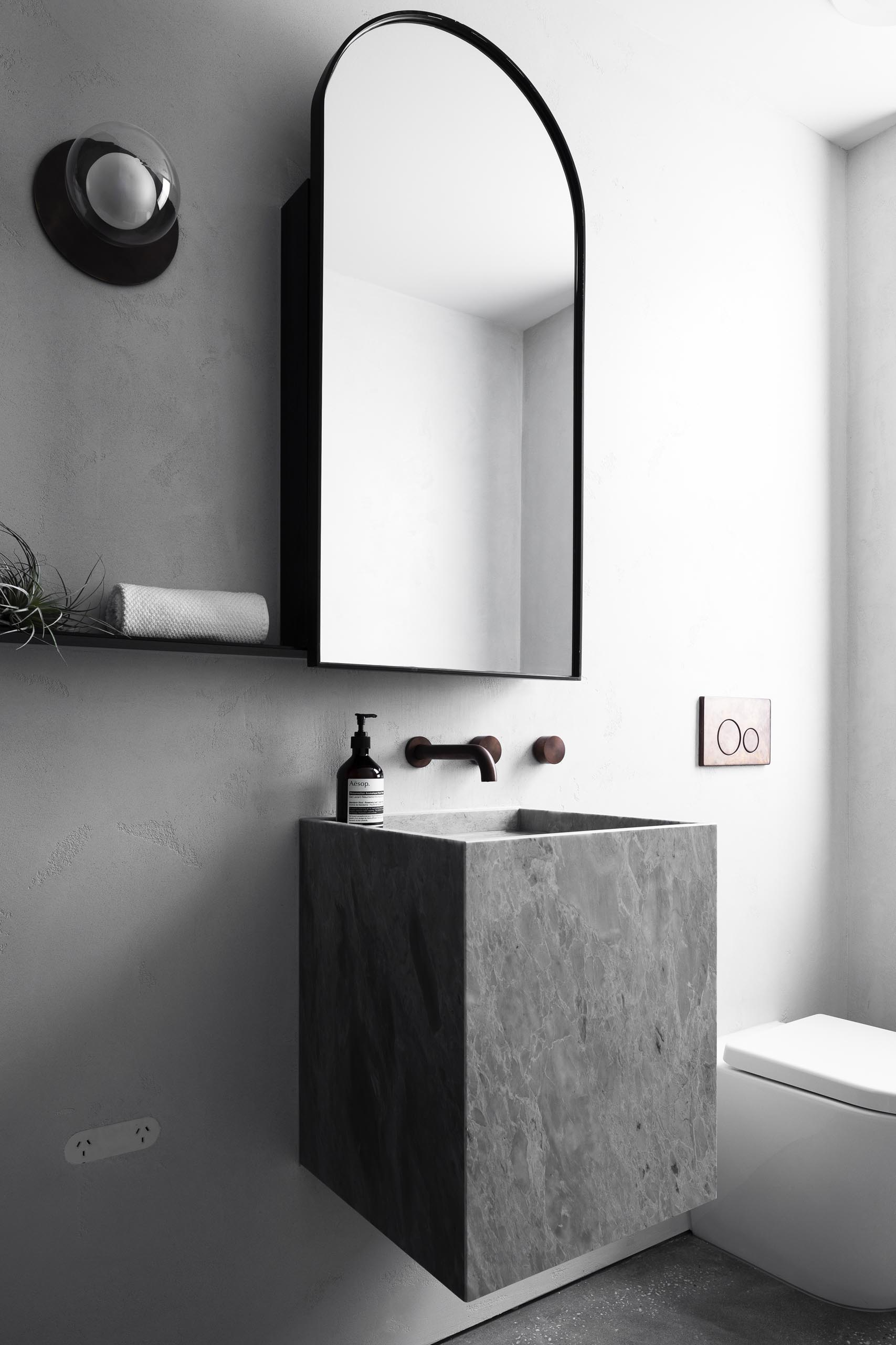 A gray bathroom with a black framed arched mirror and floating vanity.