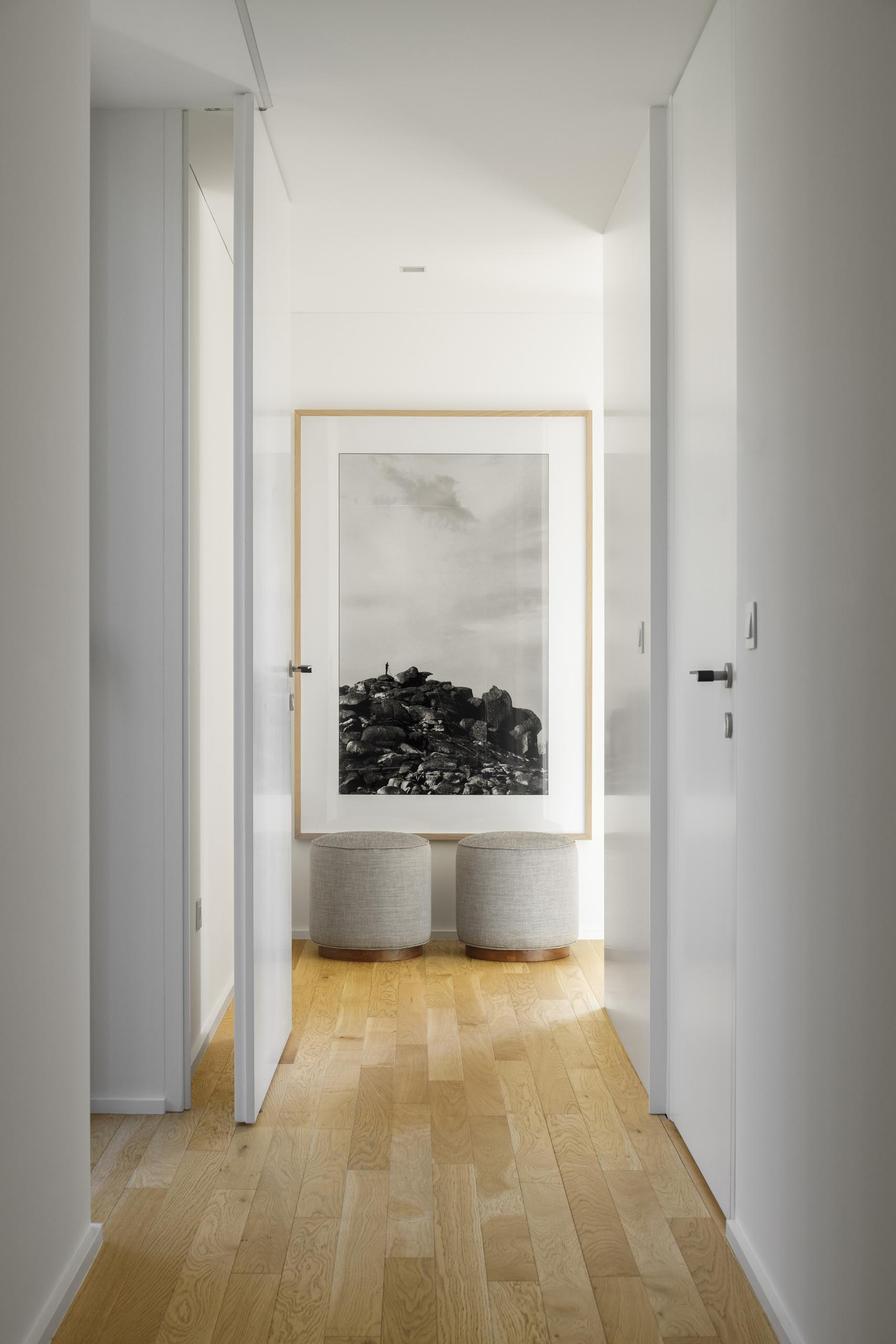 A modern white hallway with wood floors and a large vertical art print.