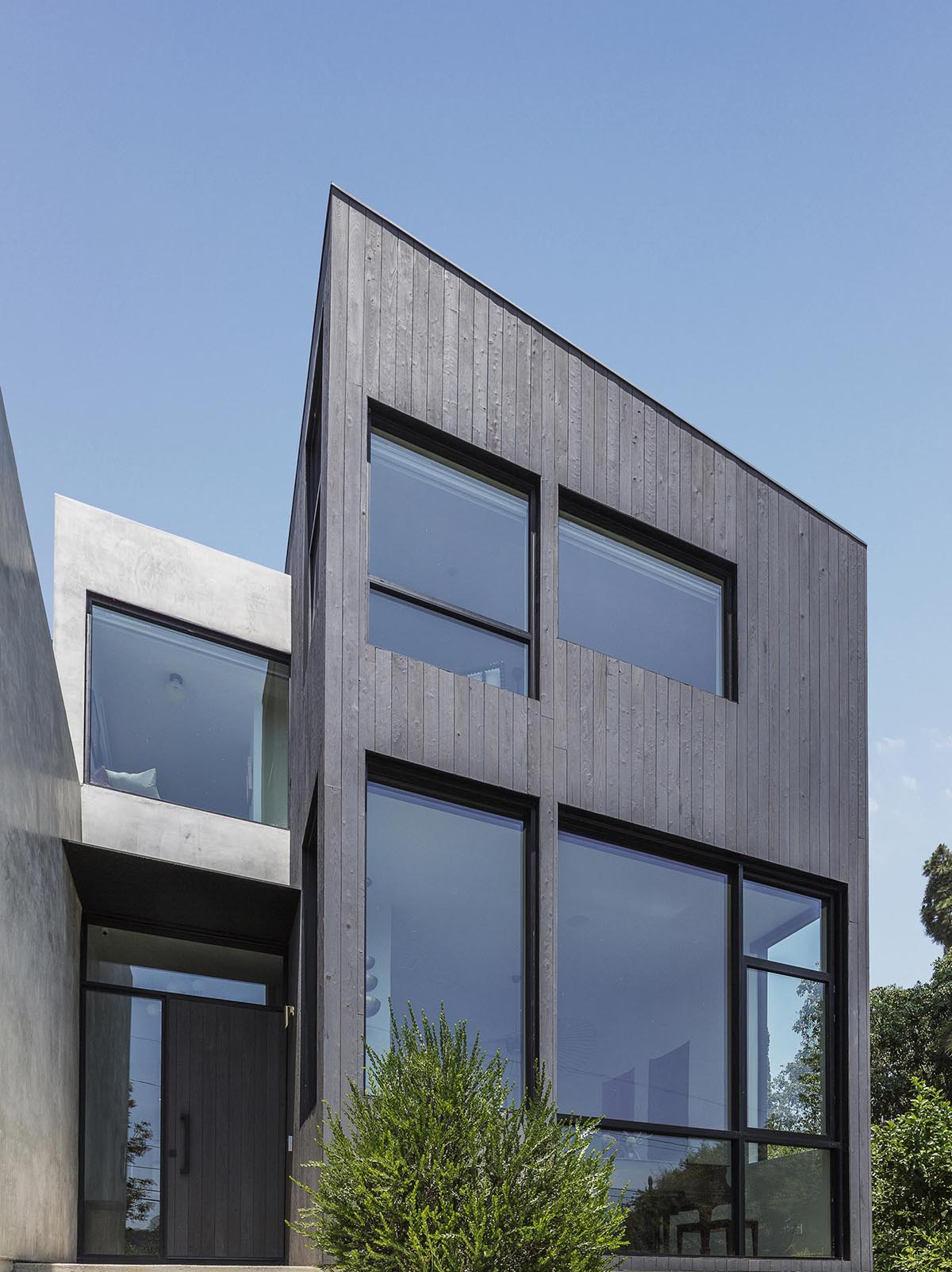 A modern house with Shou Sugi Ban charred cypress wood and a smooth exterior plaster.