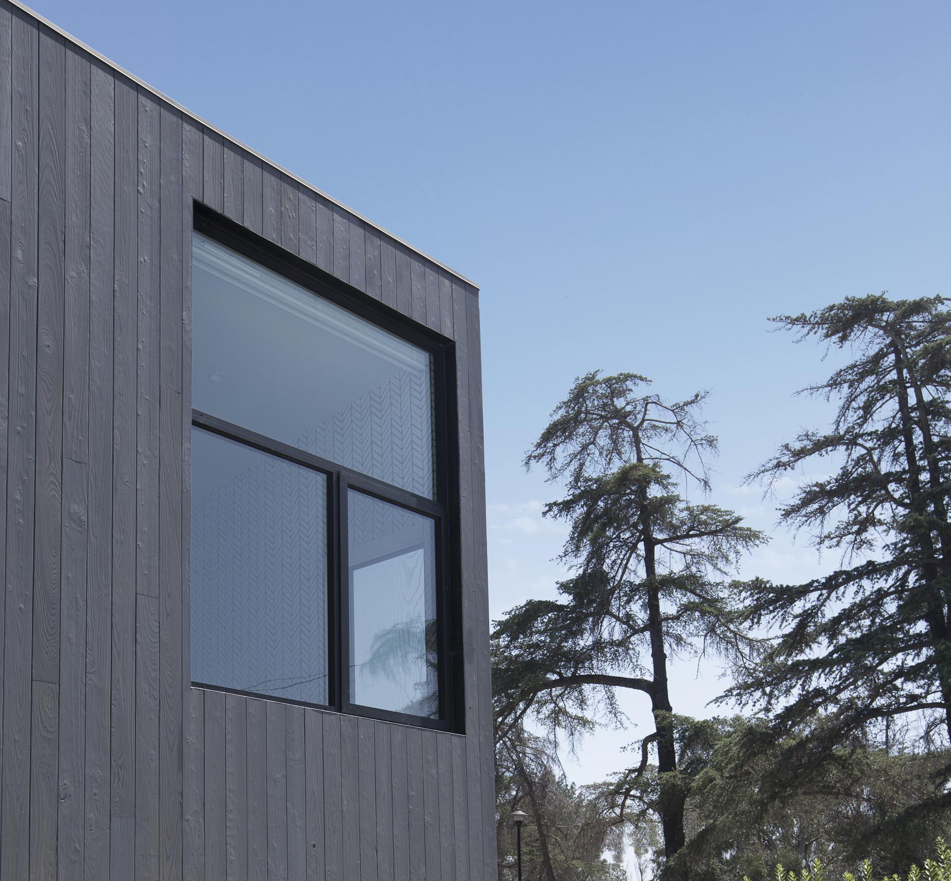 A modern home with Shou Sugi Ban exterior siding and black window frames.