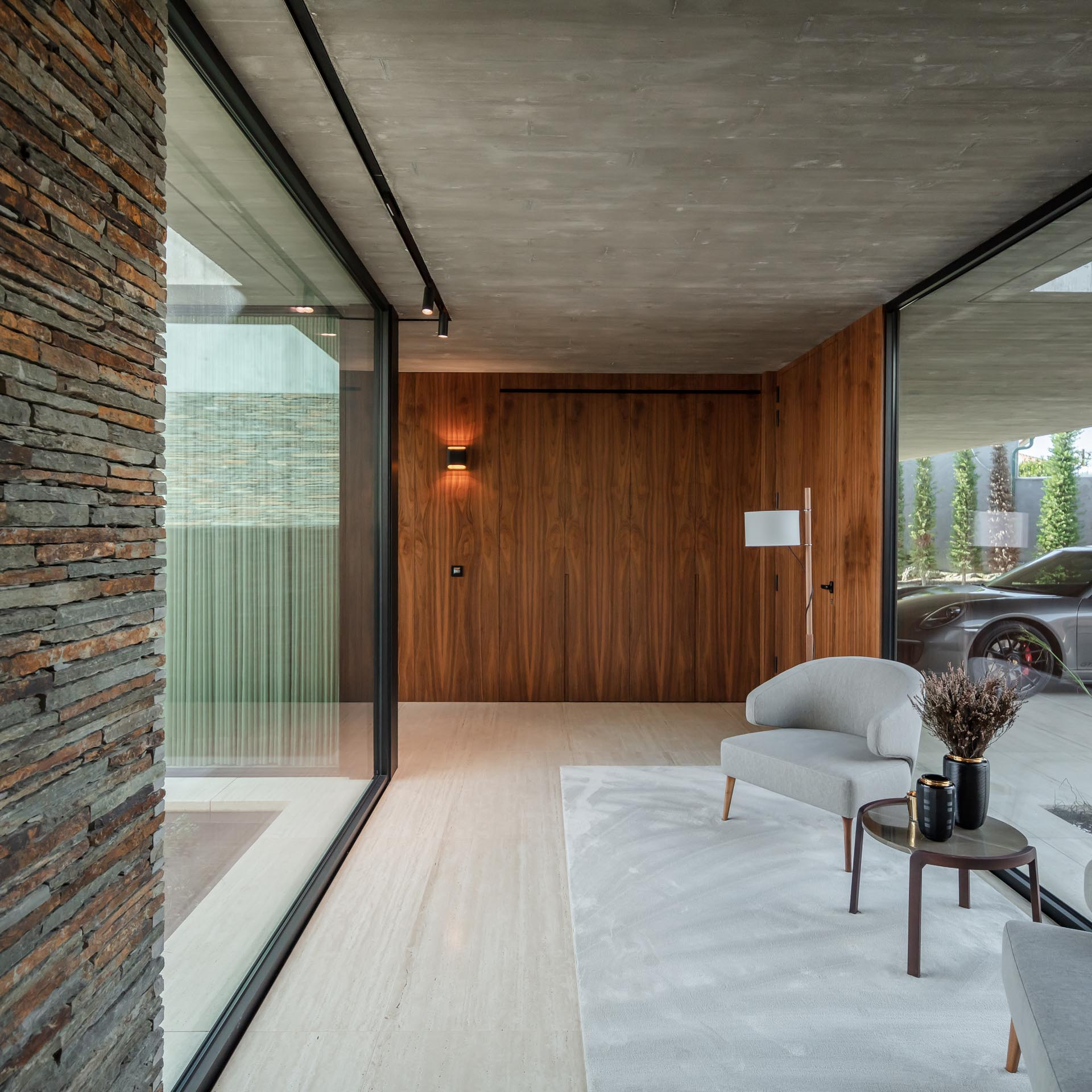 A modern entryway includes a small sitting area with floor to ceiling glass walls on either side.
