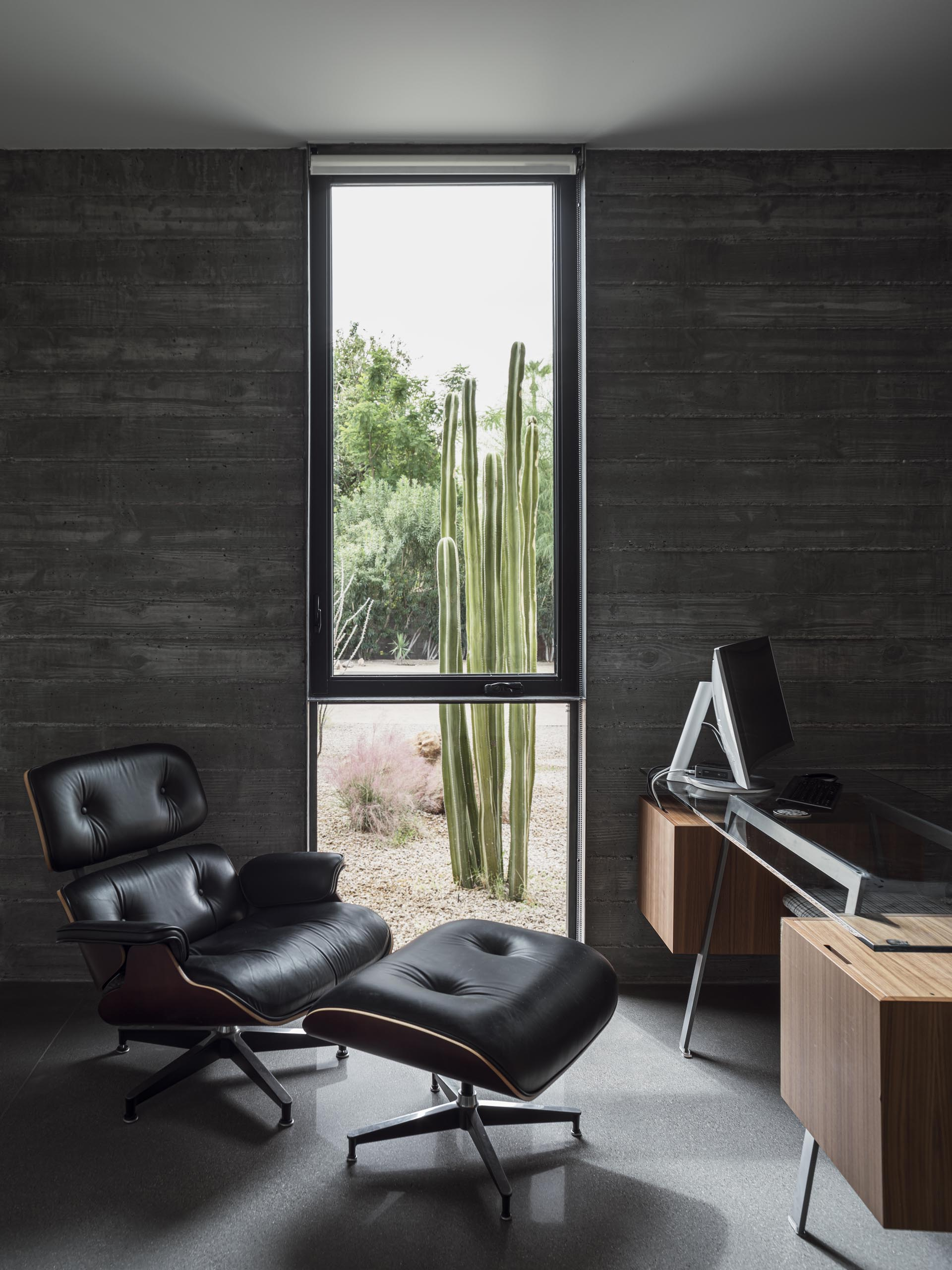 In this home office, the board formed concrete walls are clearly visible, while a floor-to-ceiling window perfectly frames the desert plants outside.