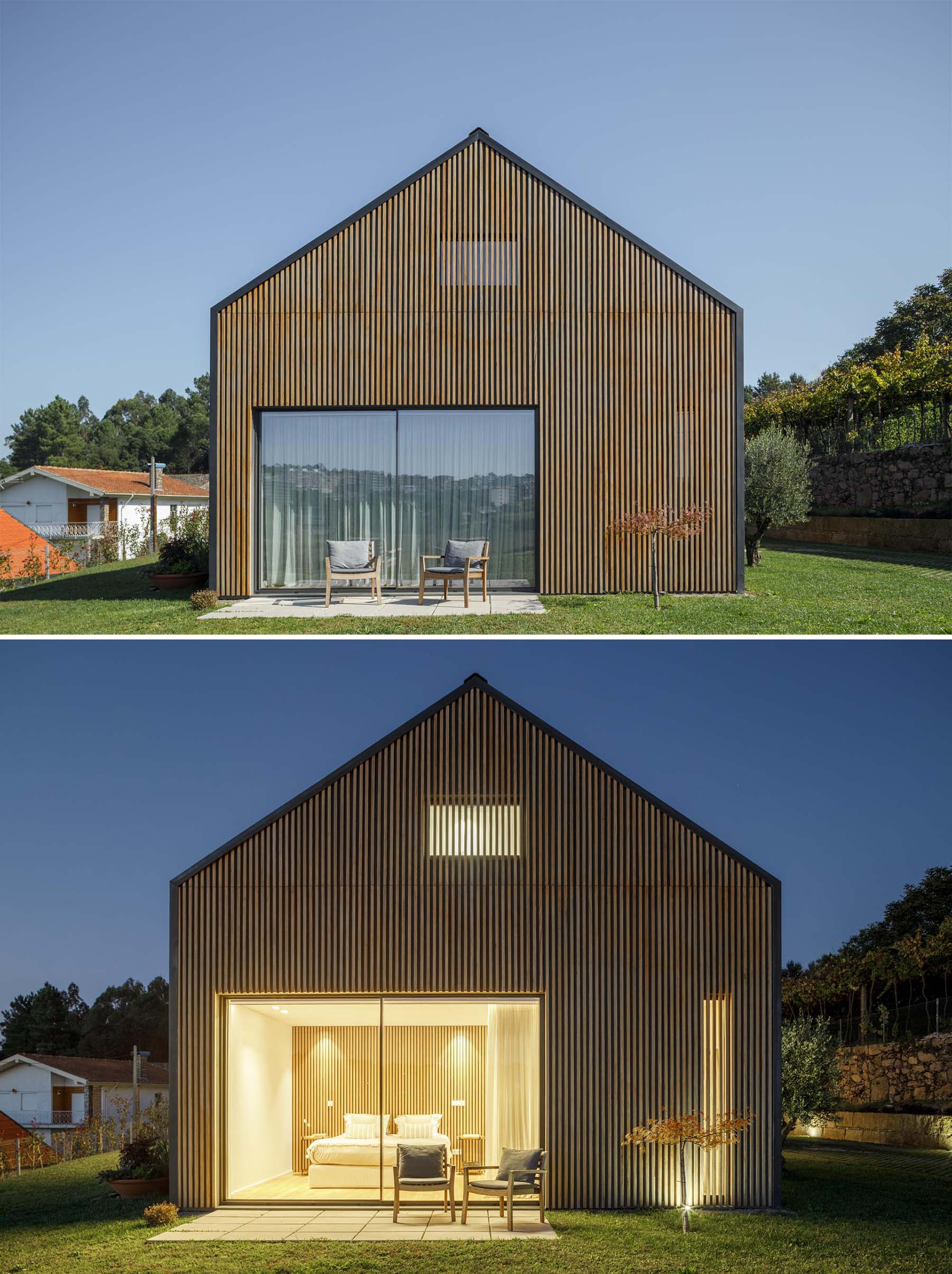 A modern home with a wood slat wall that somewhat hides a pair of windows.