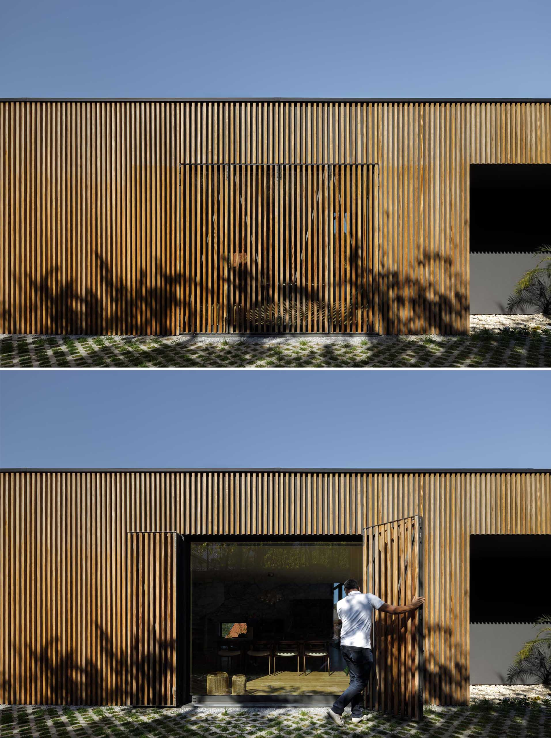 A modern home with a large window from view with a wood slat wall.