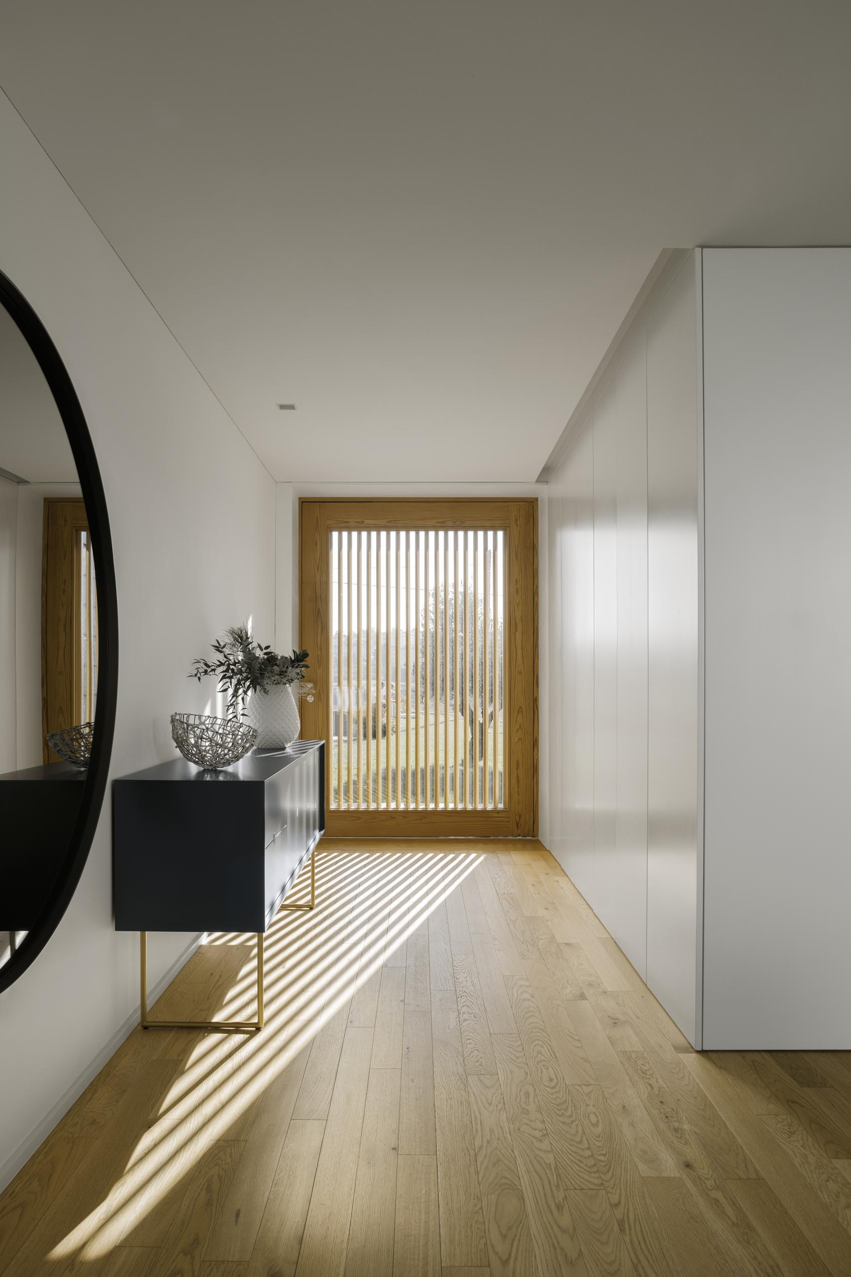 A modern home with a glass front door that allows the wood slat exterior screen to show.