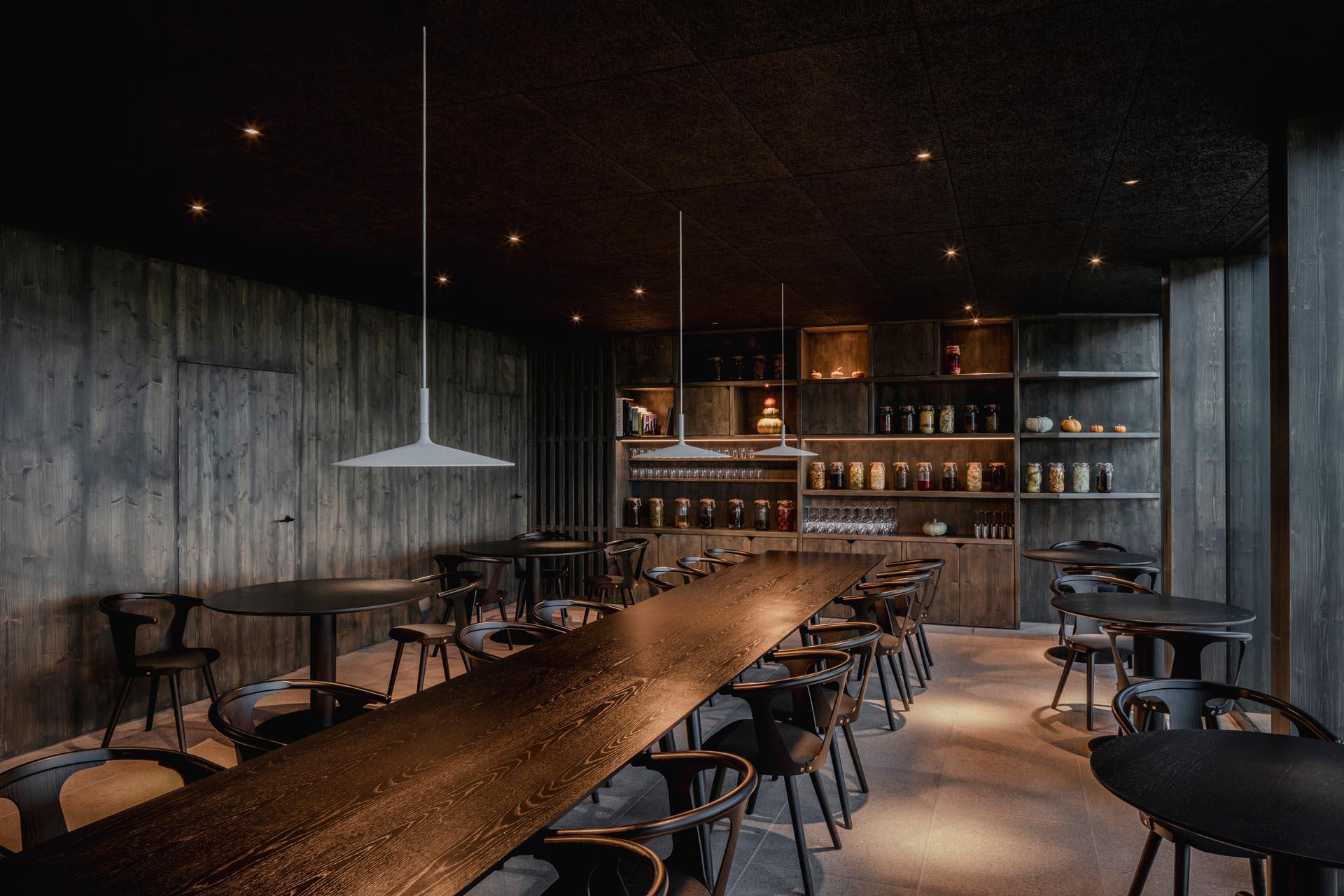 A modern hotel restaurant with a dark wood interior.