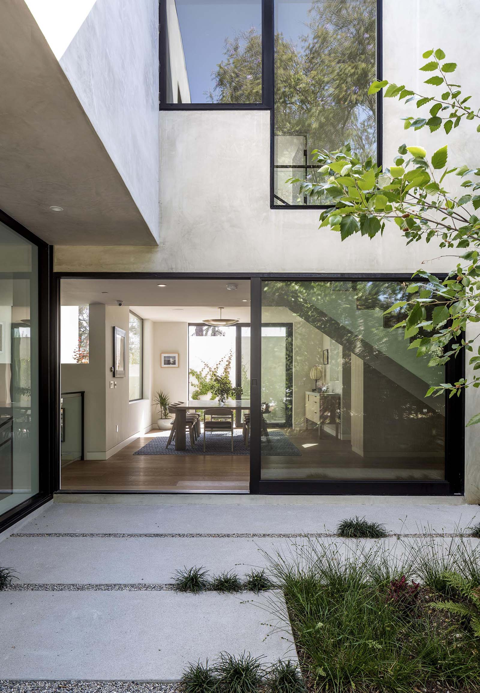 An oversized black framed sliding glass door opens the dining room to a courtyard.