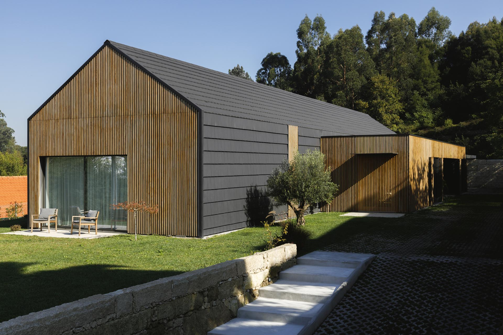 A modern black house with wood accents.